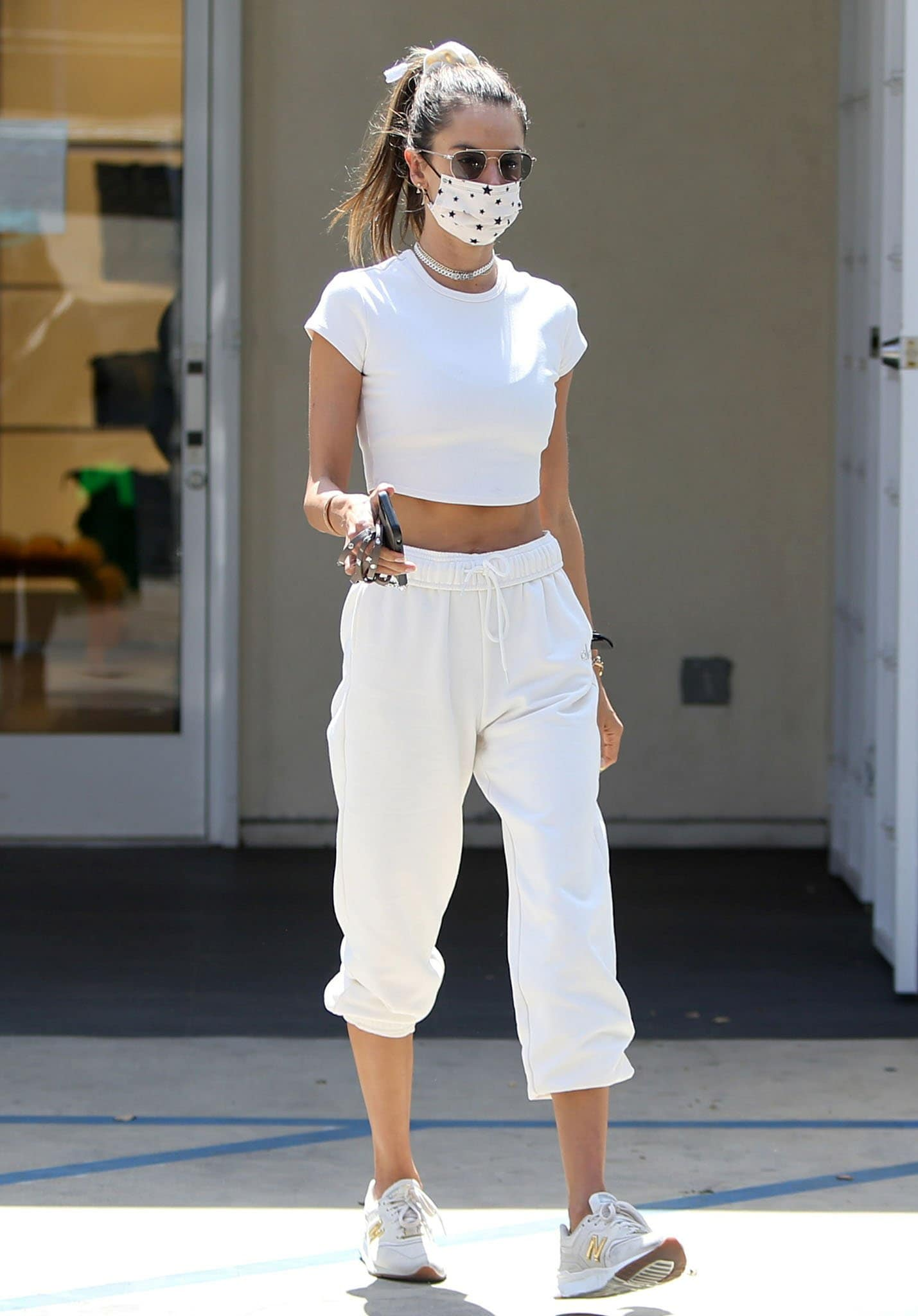 Alessandra Ambrosio puts her abs on display in a white cropped tee with white Alo sweatpants