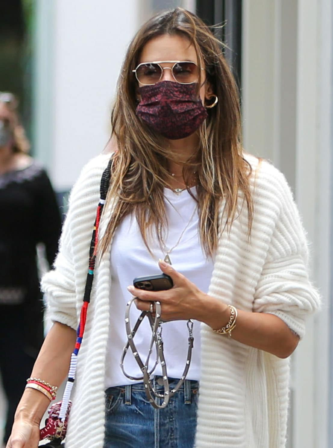 Alessandra Ambrosio looks fresh in a white tee with blue jeans and an off-white sweater