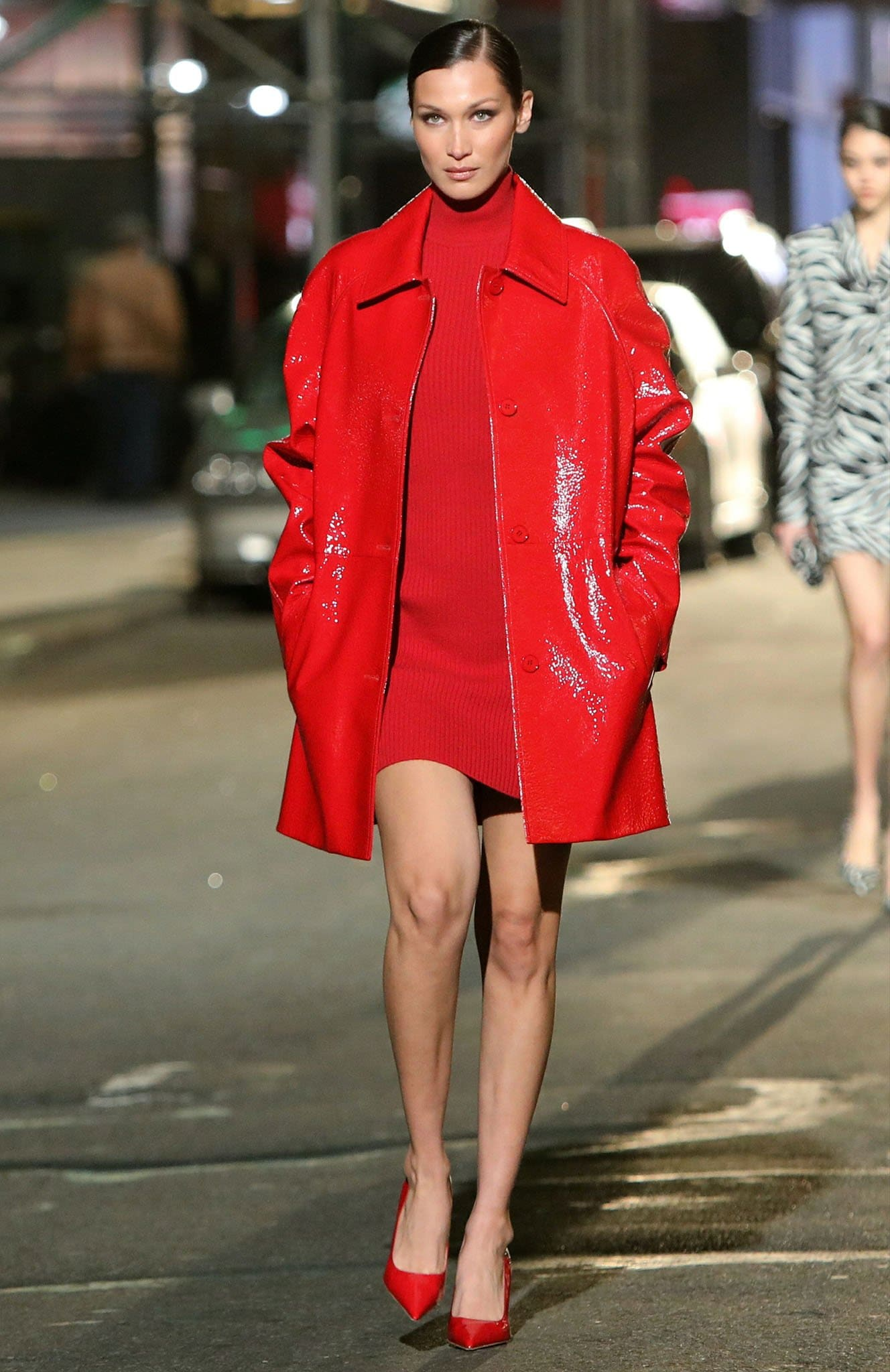 Bella Hadid bares her legs in a red mini dress and red PVC coat