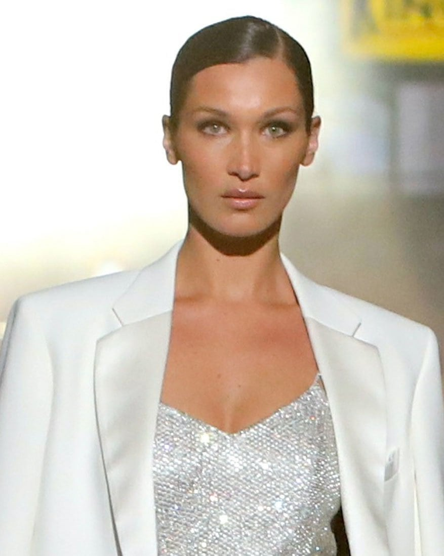 Bella Hadid styles her locks in a sleek ponytail with a deep side part and wears neutral makeup with smokey eye shadow