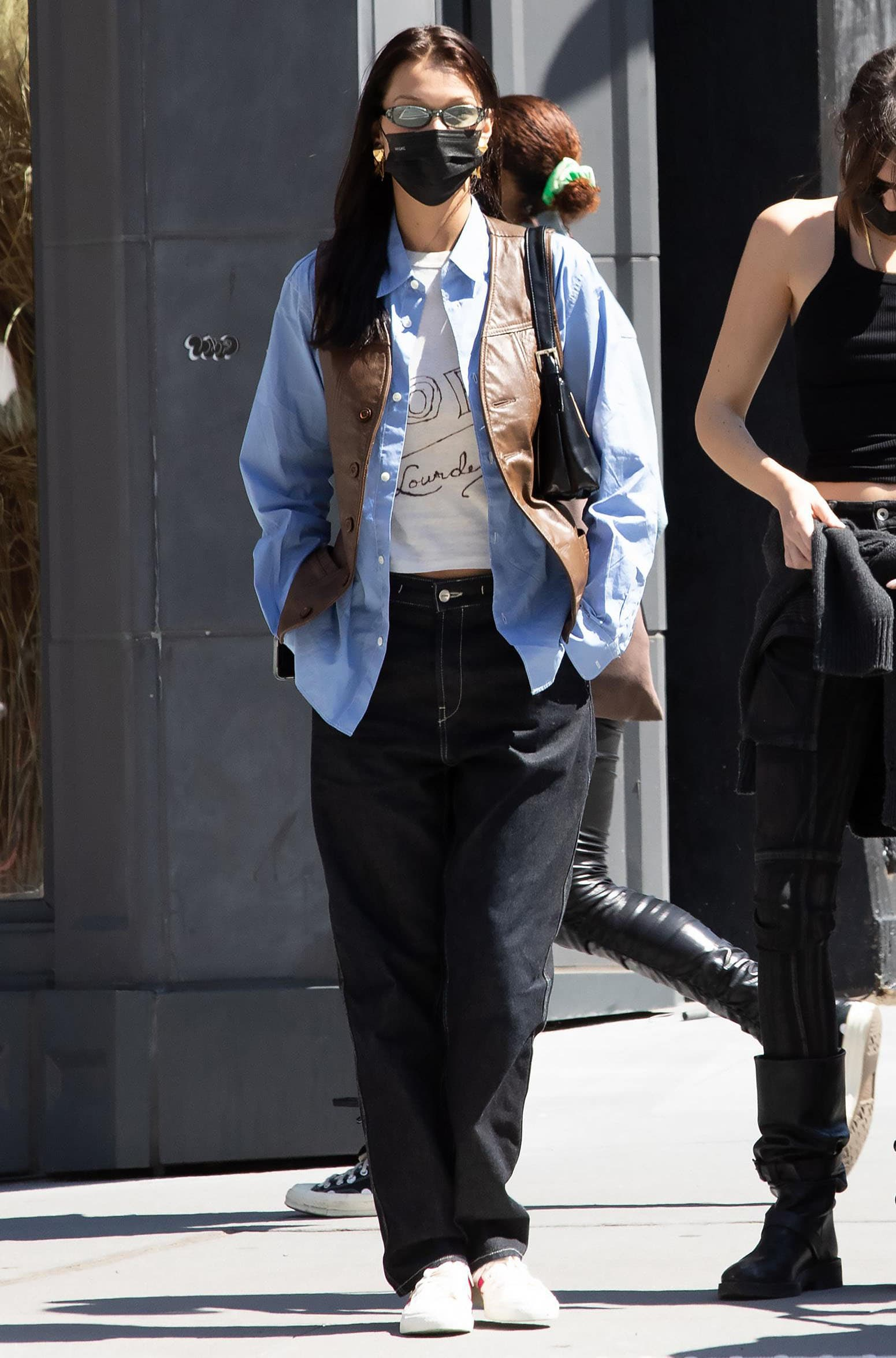 Bella Hadid goes the '90s route in crop tee and baggy jeans layered with a brown leather vest and blue button-down shirt