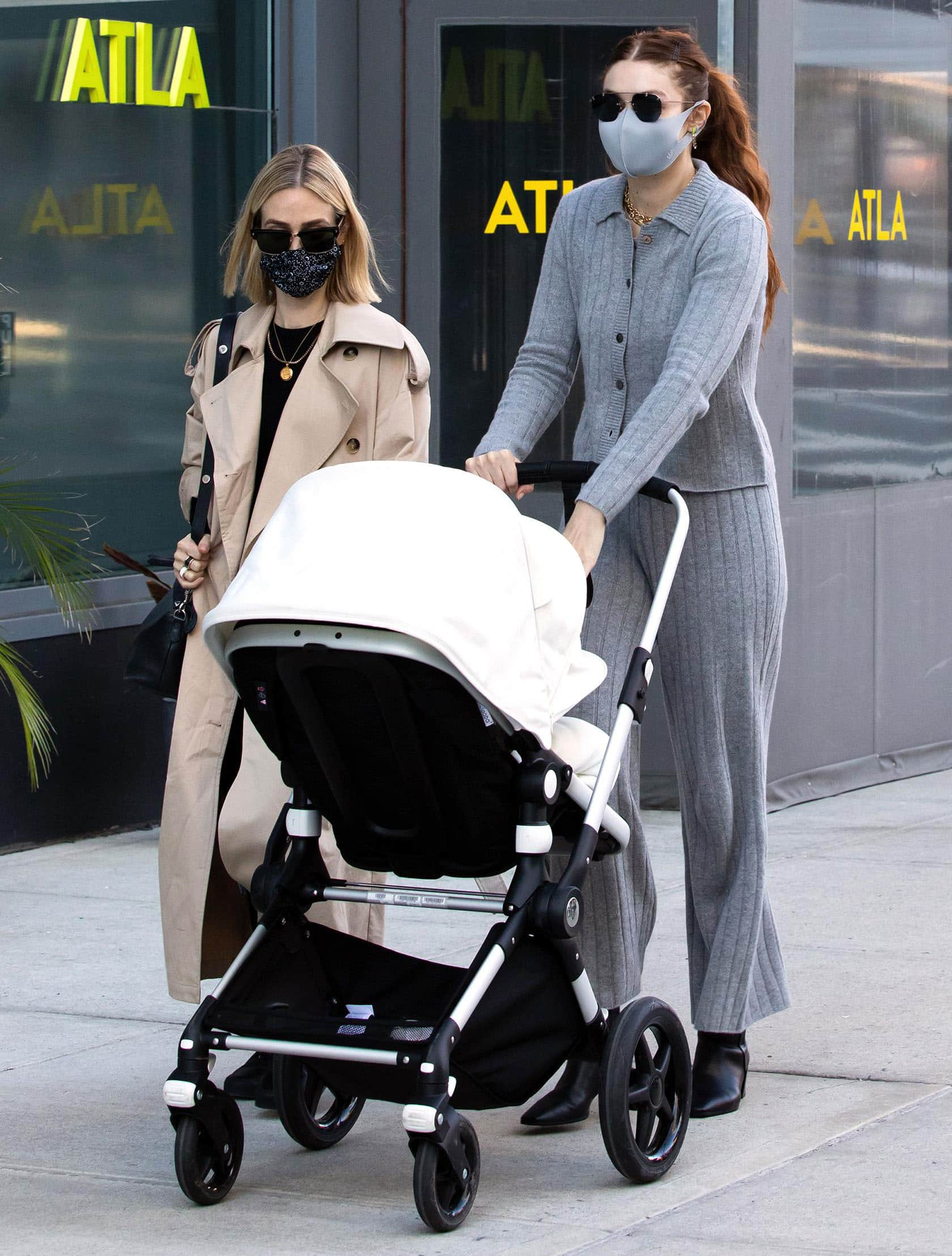 Gigi Hadid goes braless in Public Habit cashmere cardigan and wide-leg pants in New York City on March 29, 2021