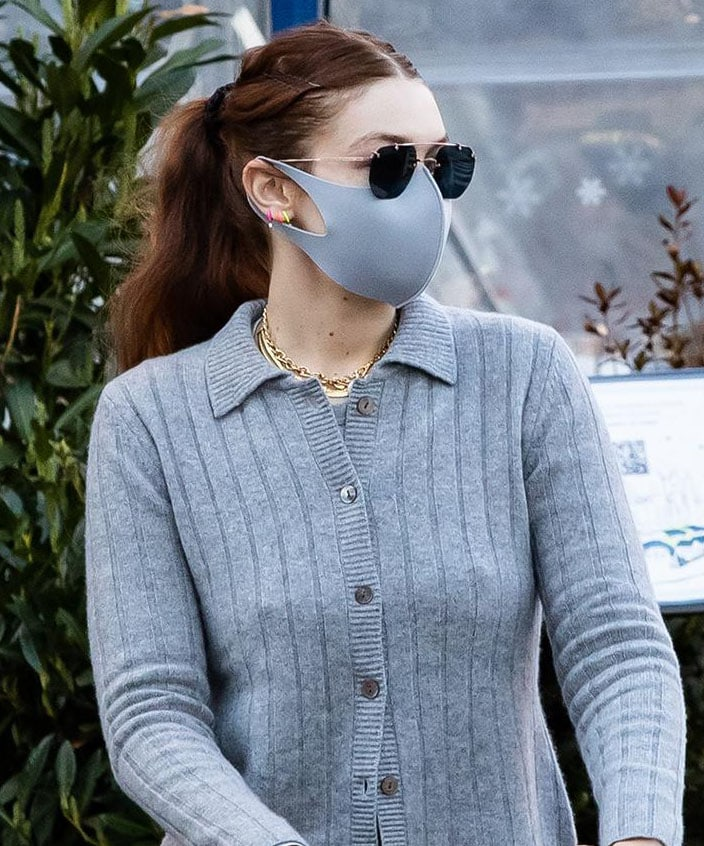 Gigi Hadid styles her long hair in a center-parted wavy ponytail and stays low profile with Lapcos face mask and Tejesta sunnies