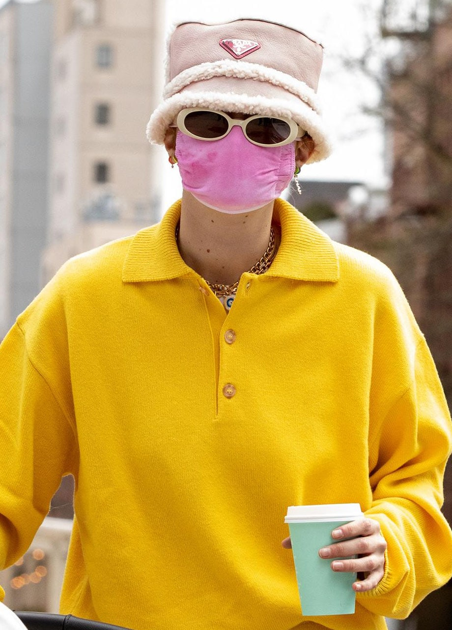 Gigi Hadid teams her yellow tracksuit with a cozy Prada fur-lined bucket hat and a pink face mask