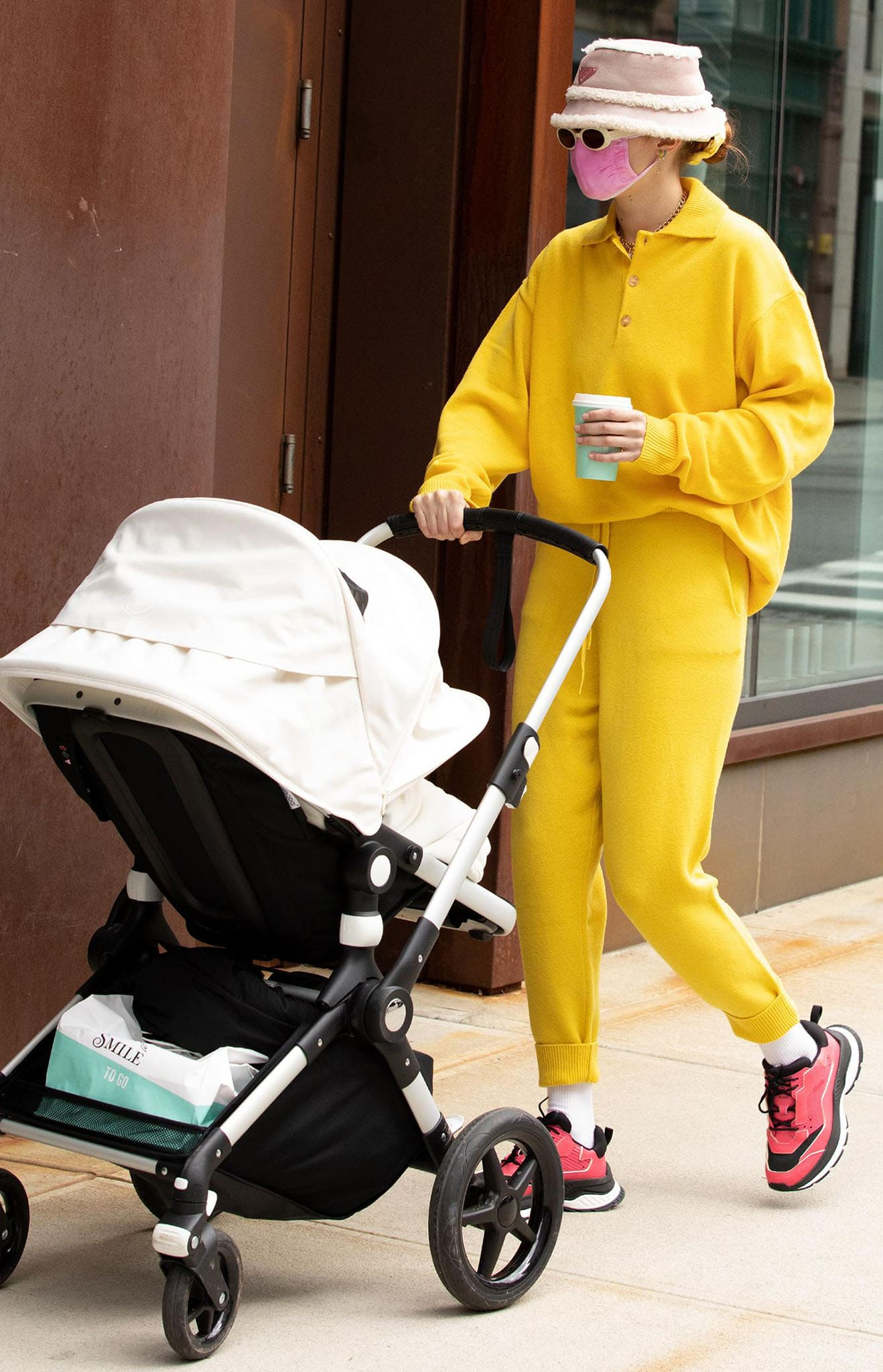 Gigi Hadid is ray of sunshine in Amiss Conception yellow polo sweater and joggers while out with daughter Khai in New York City on April 1, 2021