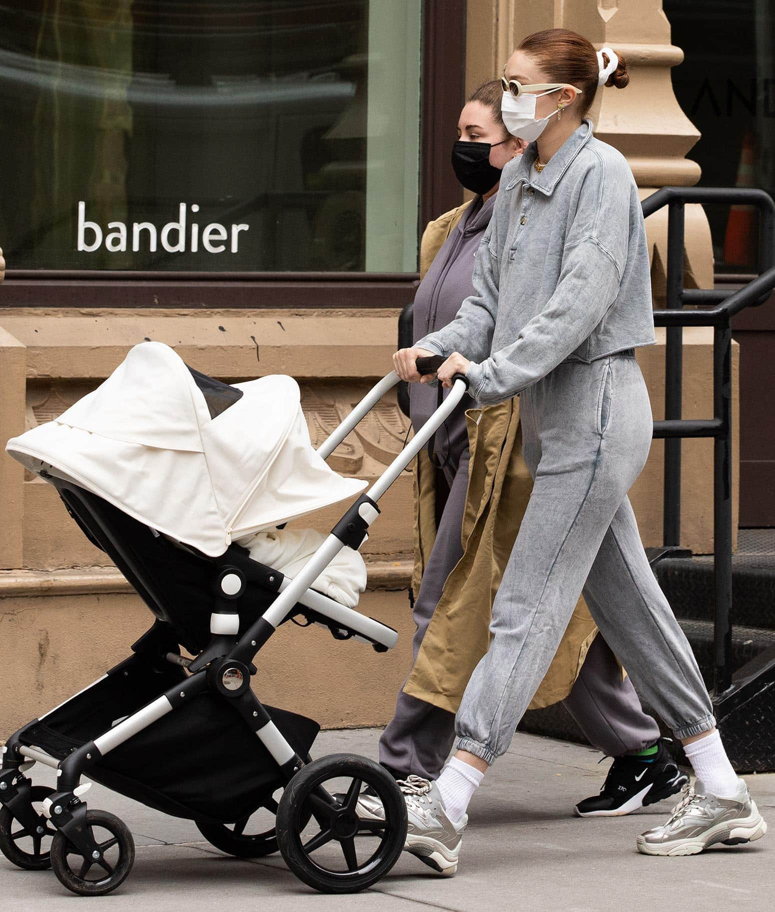 Gigi Hadid strolls with Khai in a gray polo sweater and matching joggers on March 31, 2021