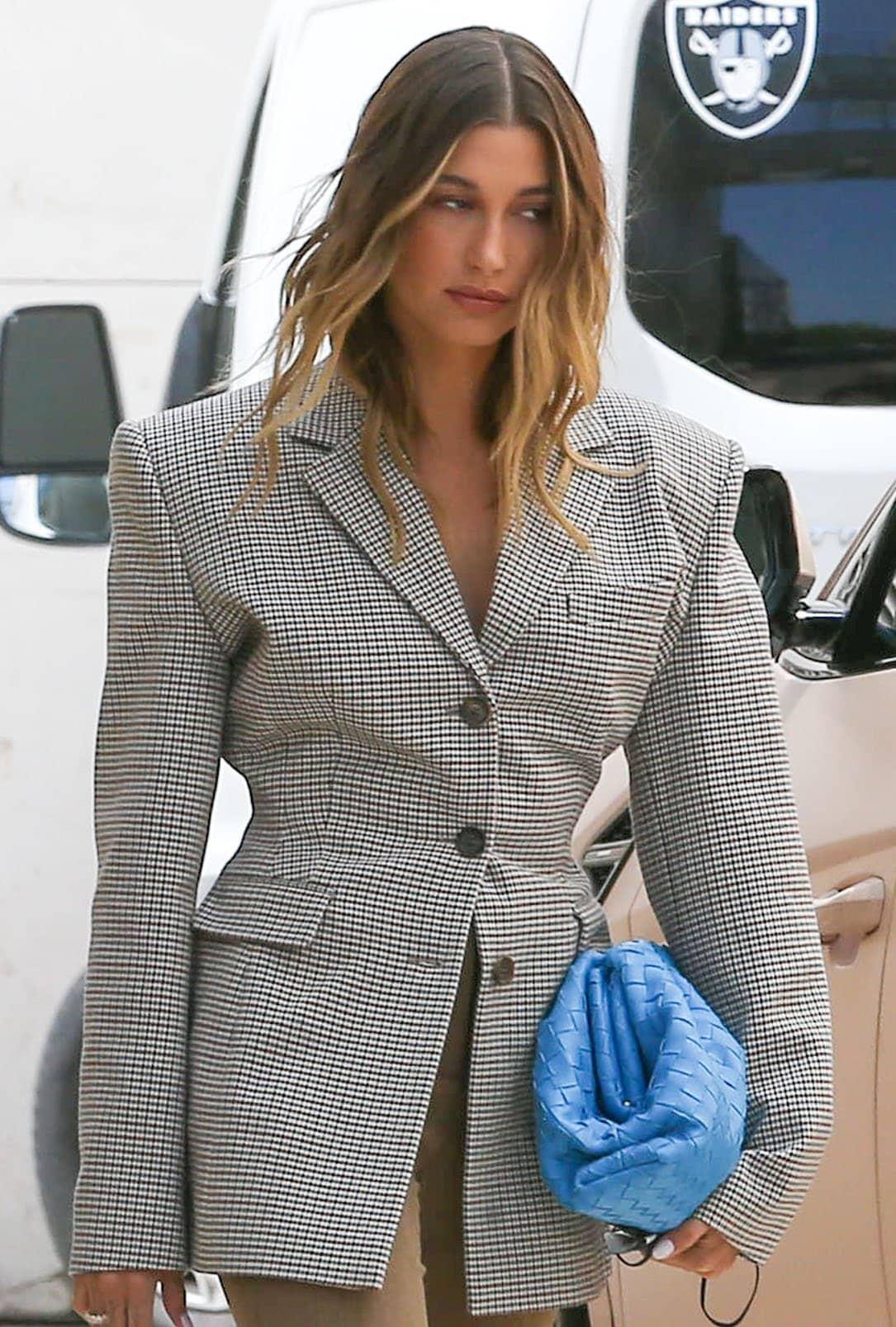 Hailey Bieber carries a blue Bottega Venetta The Pouch clutch