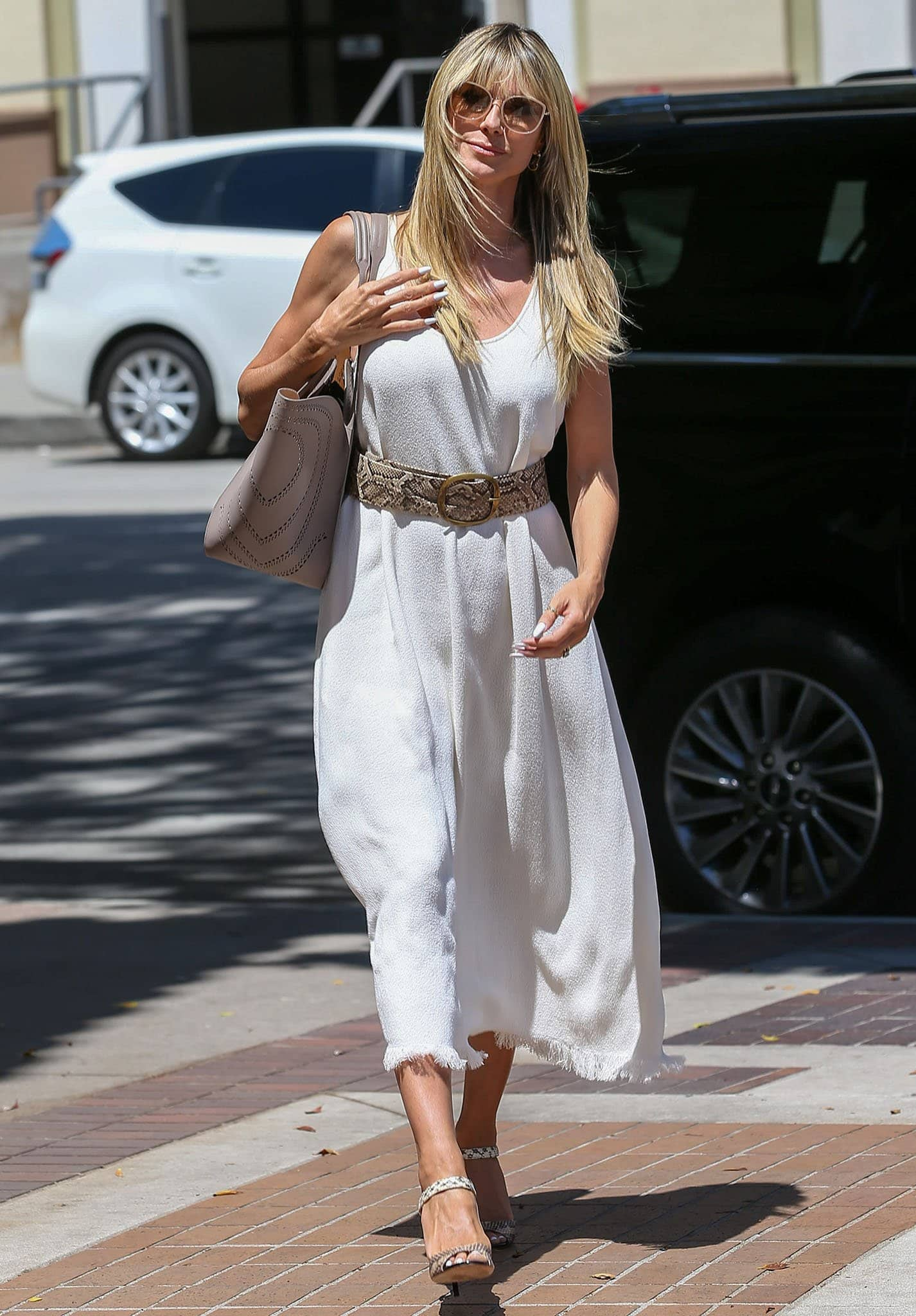 Heidi Klum goes the boho route in a white sleeveless dress with a fringed hem and a snakeskin belt on April 19, 2021