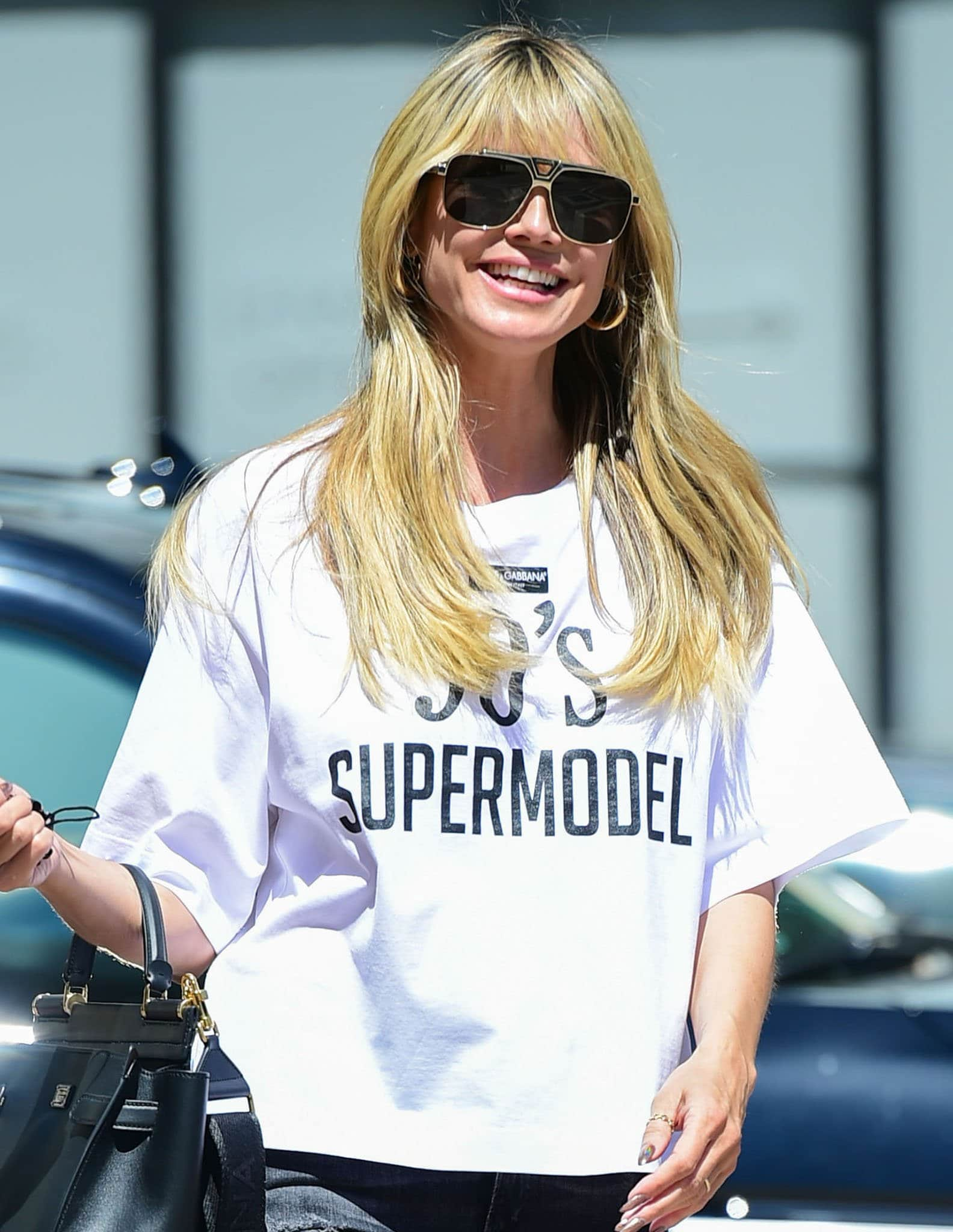 Heidi Klum styles her look with heavily tinted sunnies and chunky gold hoop earrings
