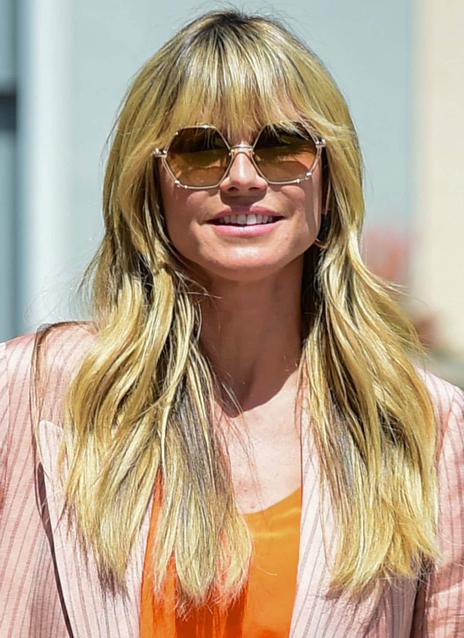Heidi Klum styles her fringe hair in loose waves and wears a pair of hexagonal sunglasses