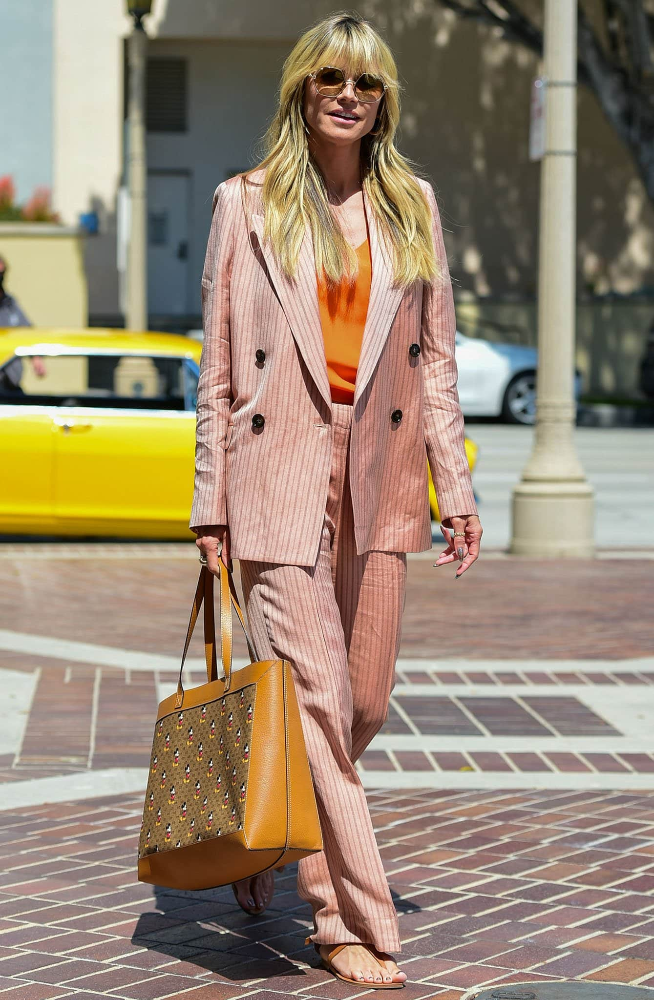 Heidi Klum continues style streak in a pink pinstripe power suit with an orange tee on March 30, 2021