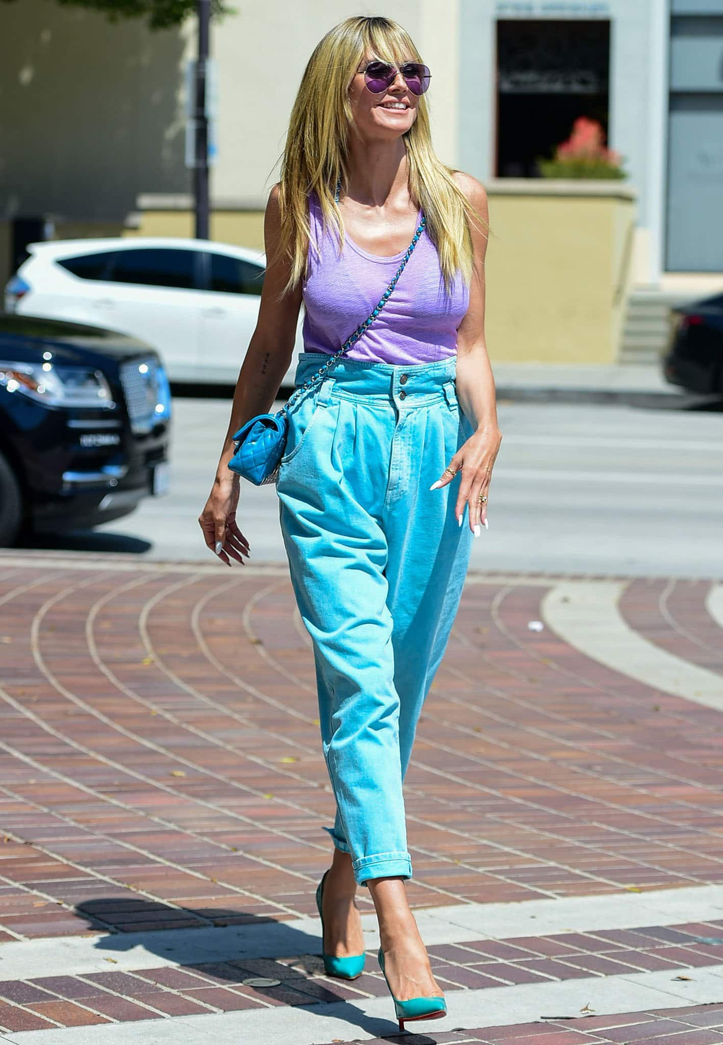 Heidi Klum plays with pastel and displays her boobs in a purple tank top with Gucci cyan jeans
