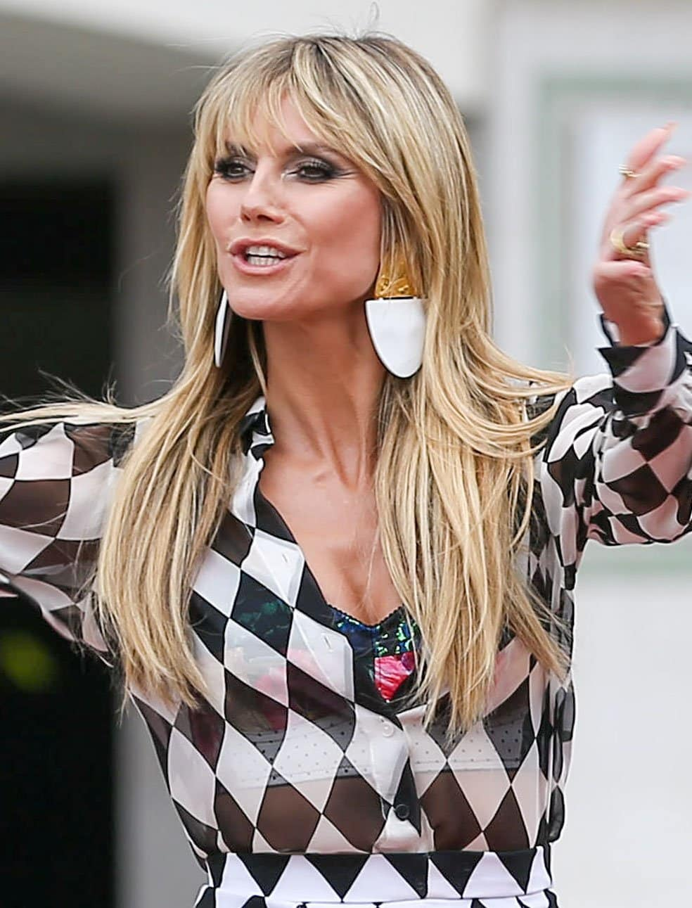Heidi Klum accessorizes with oversized earrings and glams up with smokey eyes and nude lipstick