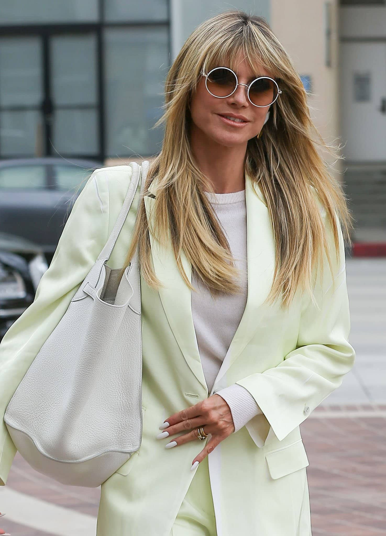 Heidi Klum styles her look with round white-framed sunnies and a large Celine tote