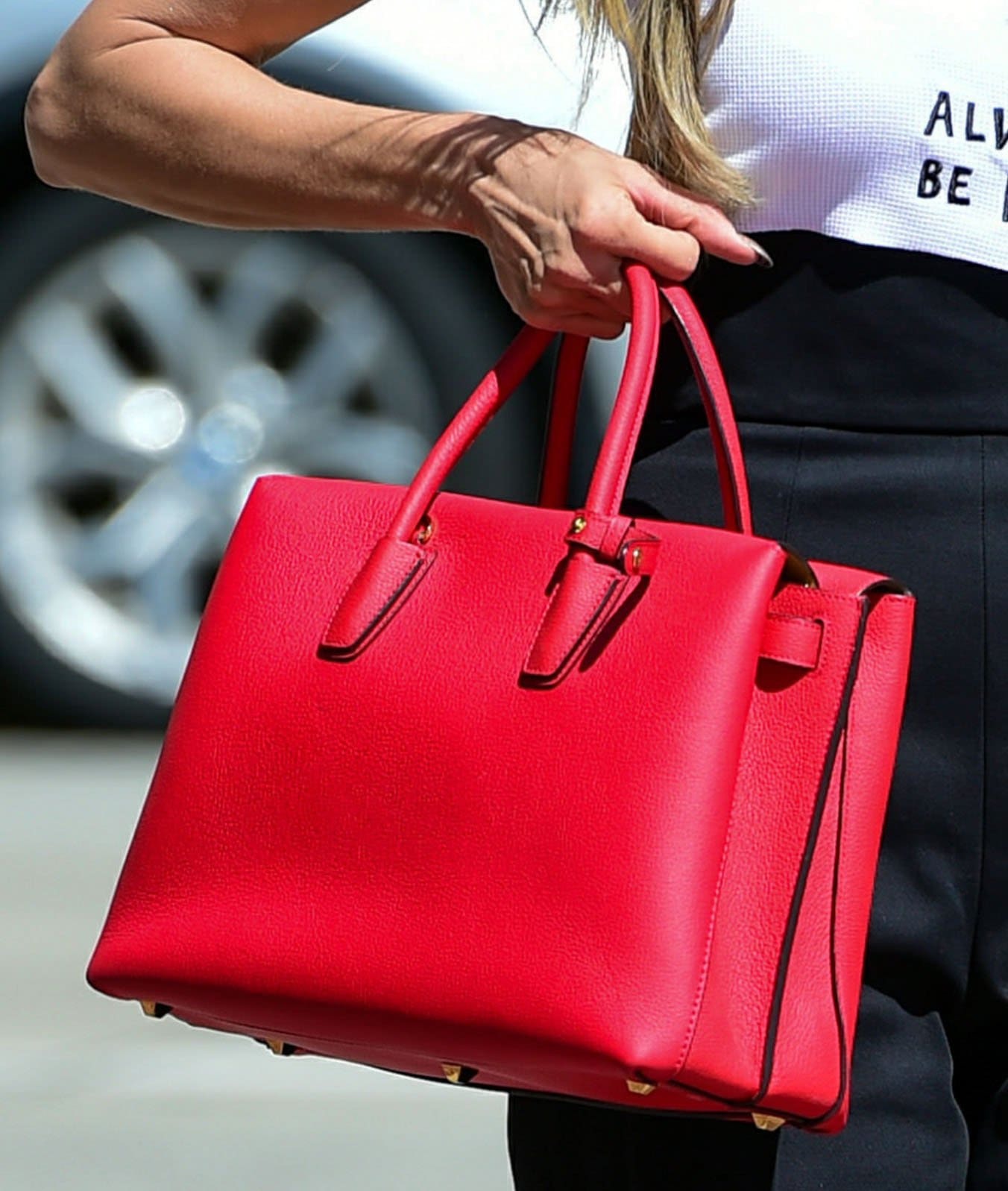 Heidi Klum adds color to her look with a ruby red MCM Milla tote bag