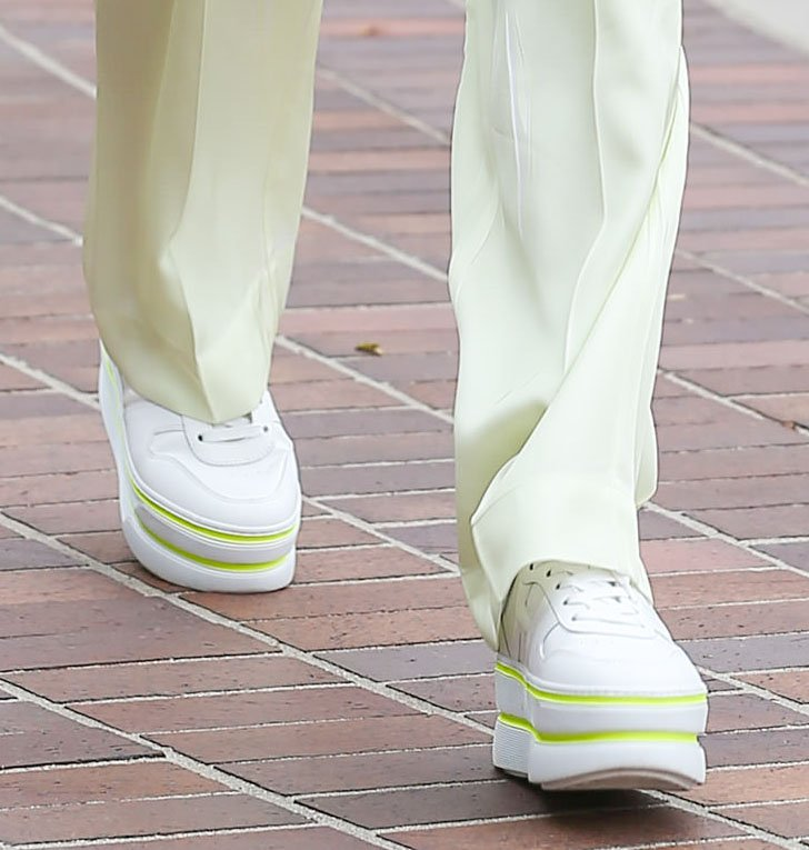 Heidi Klum dresses down her pantsuit with chunky white Hogan sneakers with neon striped trims
