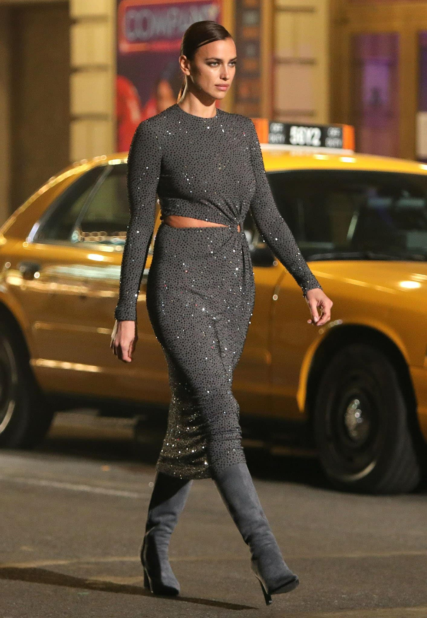 Irina Shayk showcases her model figure in a curve-hugging crystal-embellished dress with knee-high boots
