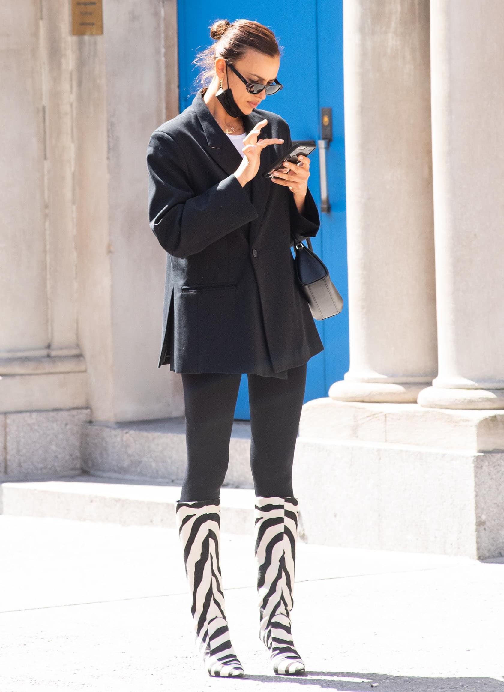 Irina Shayk layers up in Paris Georgia boxy blazer with white tee and Calzedonia leggings
