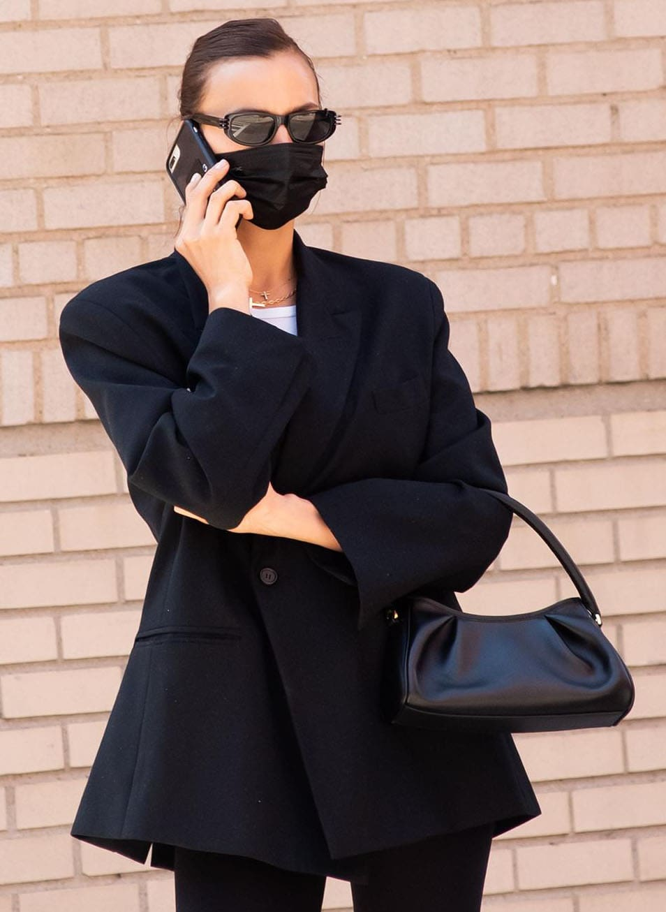 Irina Shayk wears her hair up in a bun and covers her face with black face mask and Givenchy's Pierced Amina sunglasses