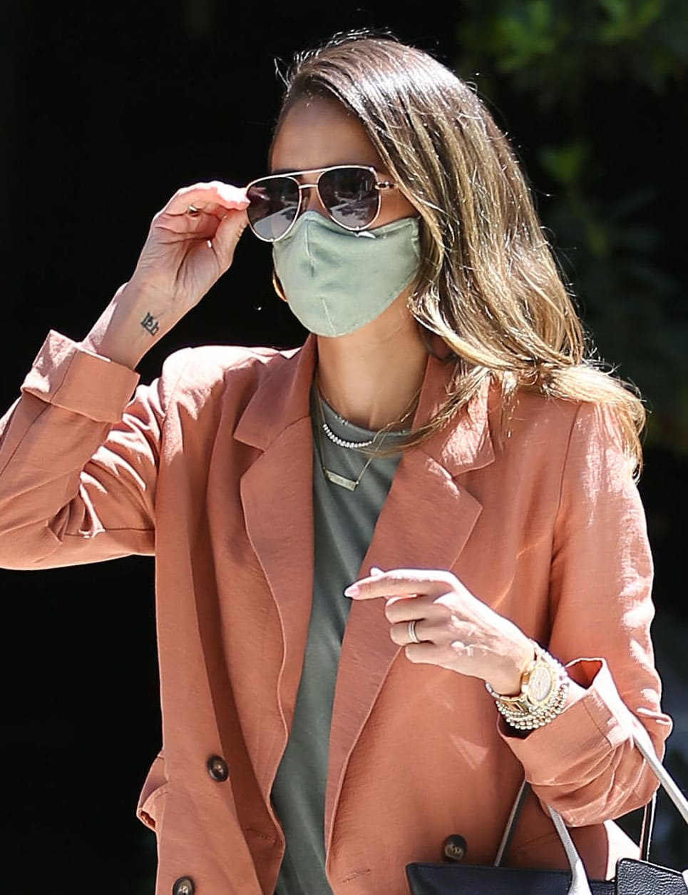Jessica Alba wears her honey tresses down and covers her face with gold-framed sunnies and green face mask
