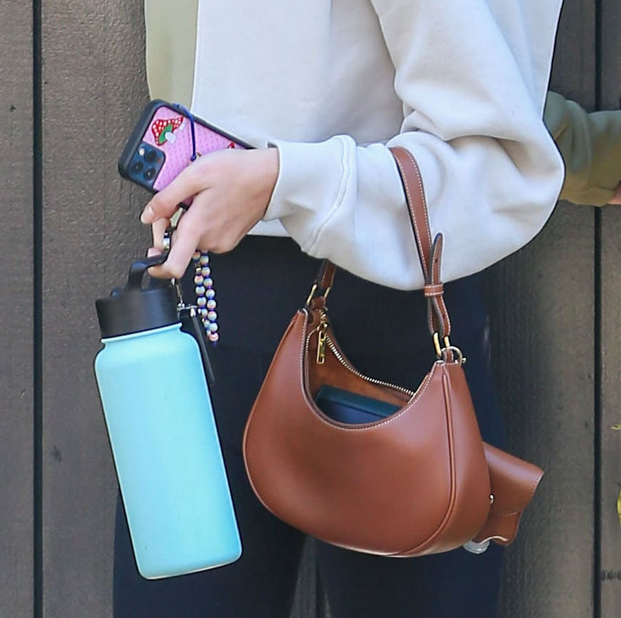 Kaia Gerber carries a Celine bag with Simple Modern Summit water bottle and her iPhone in Wildflower Shrooms phone case