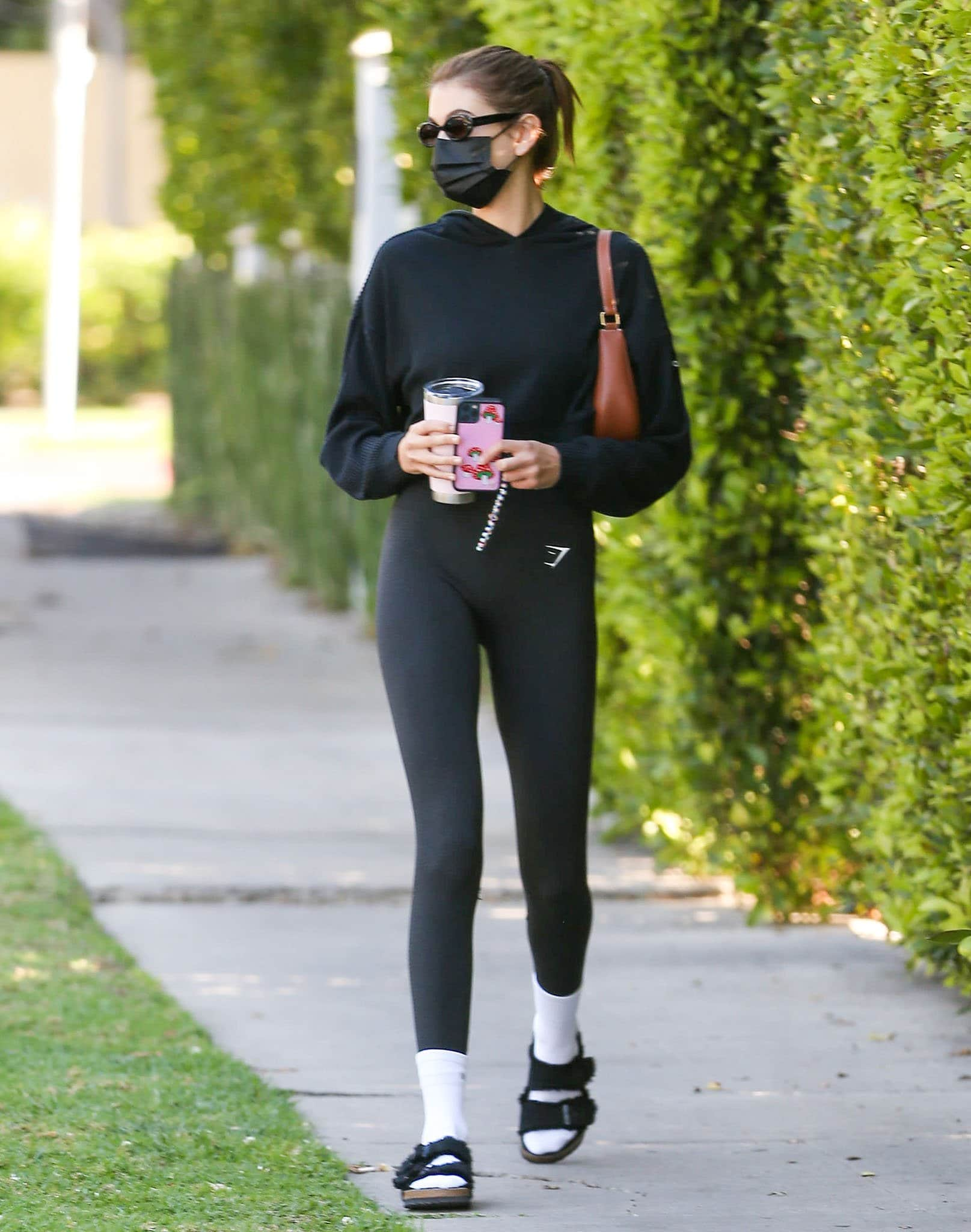 Kaia Gerber wears her furry Birks with Active Set white socks, Gymshark leggings, and Alo Yoga hoodie on April 1, 2021