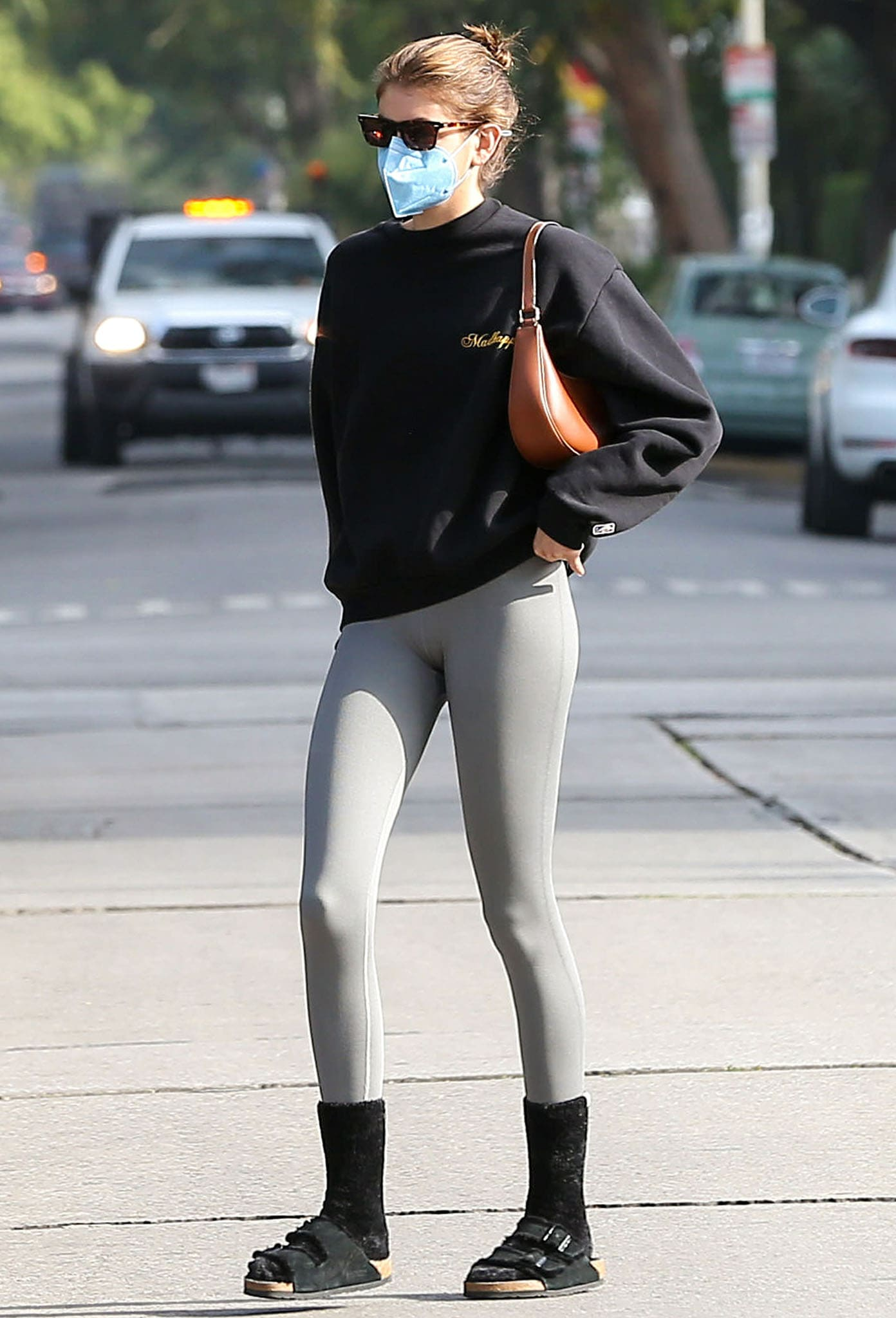 Kaia Gerber teams a black Madhappy Lakers sweatshirt with fitted gray leggings