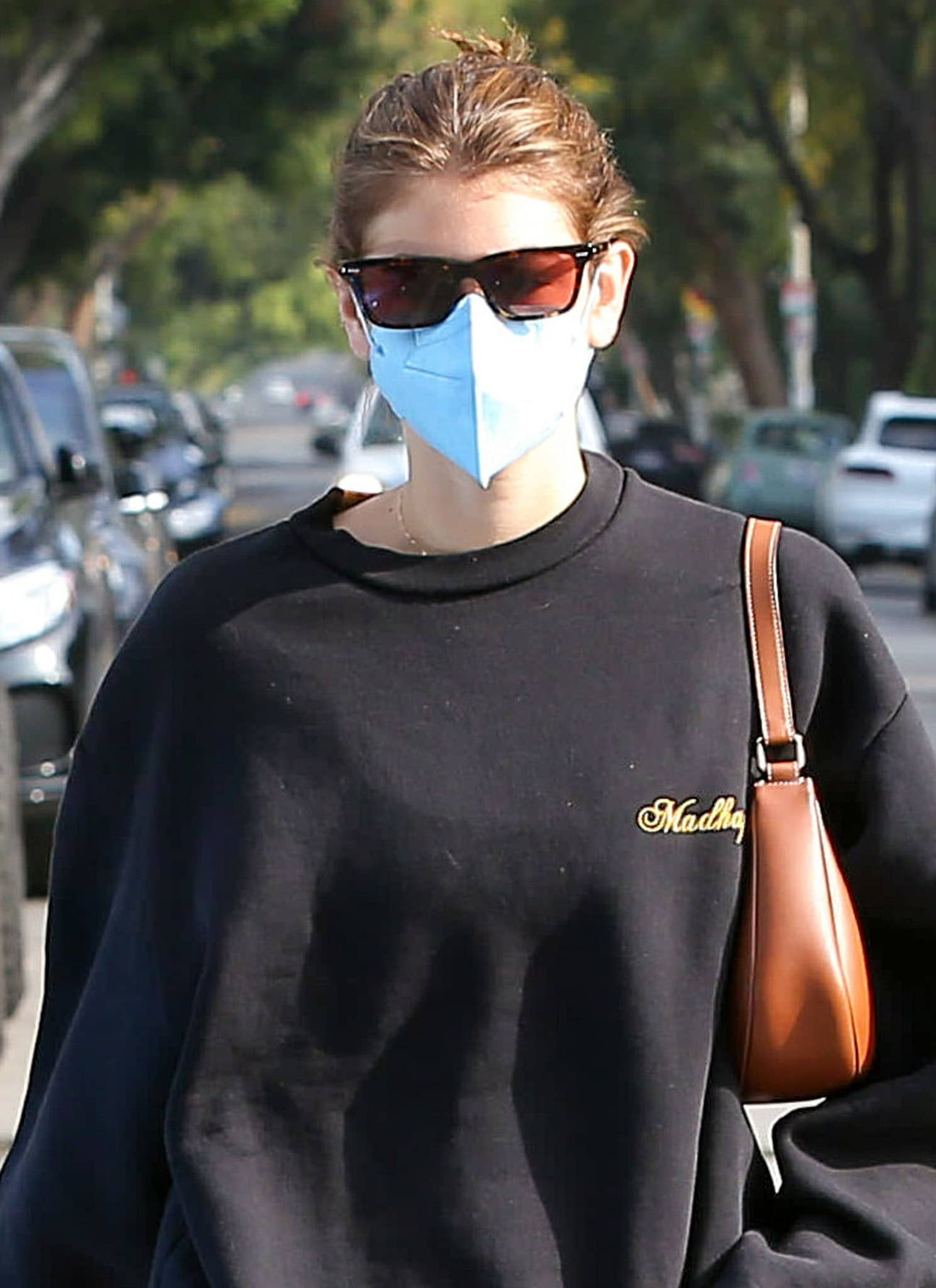 Kaia Gerber pulls her hair into a casual bun and hides her eyes behind The Row x Oliver Peoples BA CC acetate sunglasses