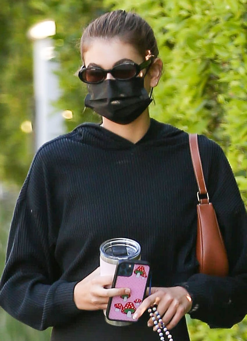Kaia Gerber pulls tresses into a high ponytail and covers her face with oval-framed sunglasses and a black face mask