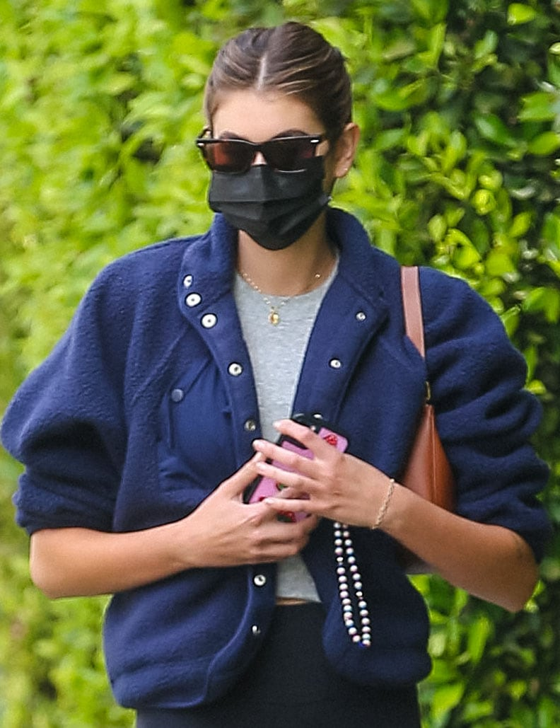 Kaia Gerber wears a ponytail and styles with tortoiseshell sunglasses, a Celine bag, and a black face mask