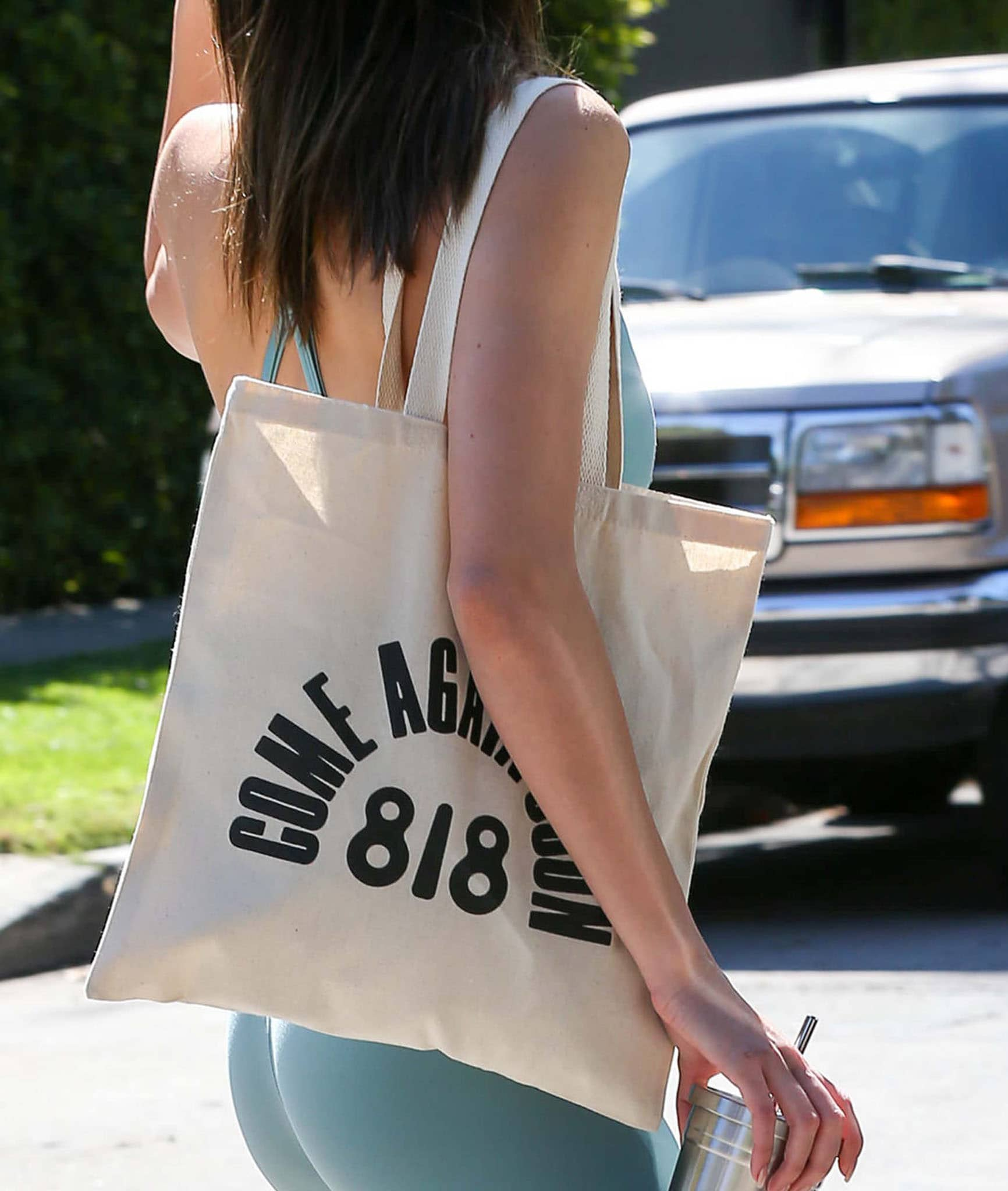 """Kendall Jenner carries a canvas tote bag featuring """"Come Again Soon 818"""" for her tequila brand"""