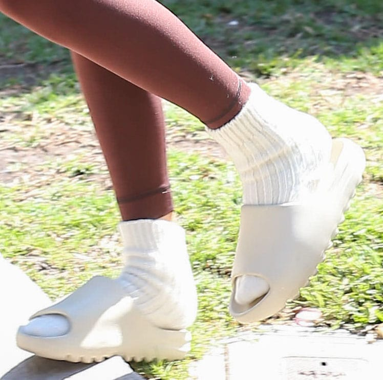 Kendall Jenner slips into a pair of white socks and Yeezy slides