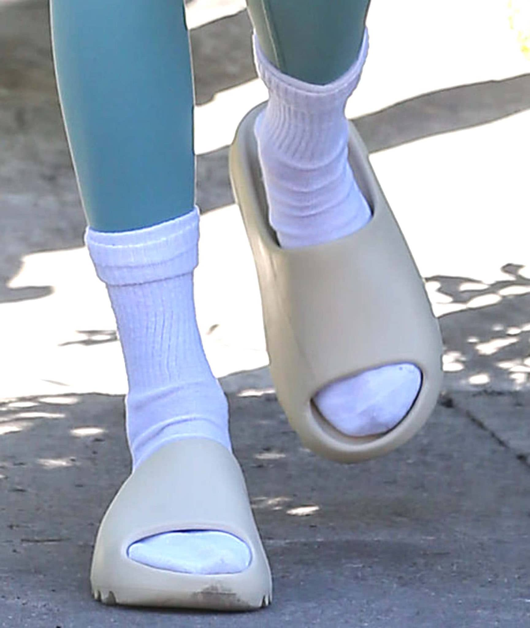 Kendall Jenner wears white socks with Yeezy slides in bone colorway