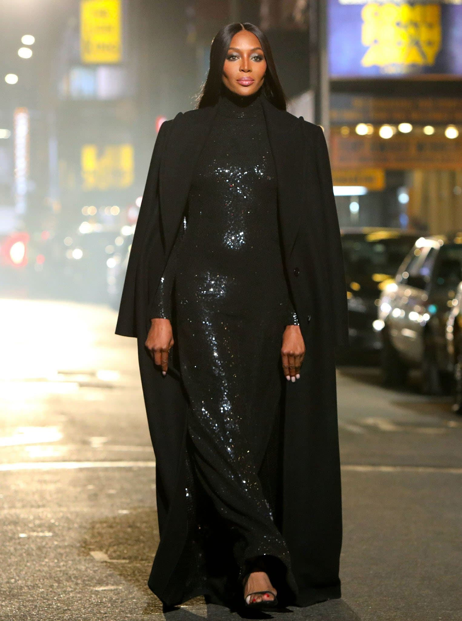 Naomi Campbell looks regal in a long black sequined gown and floor-length coat