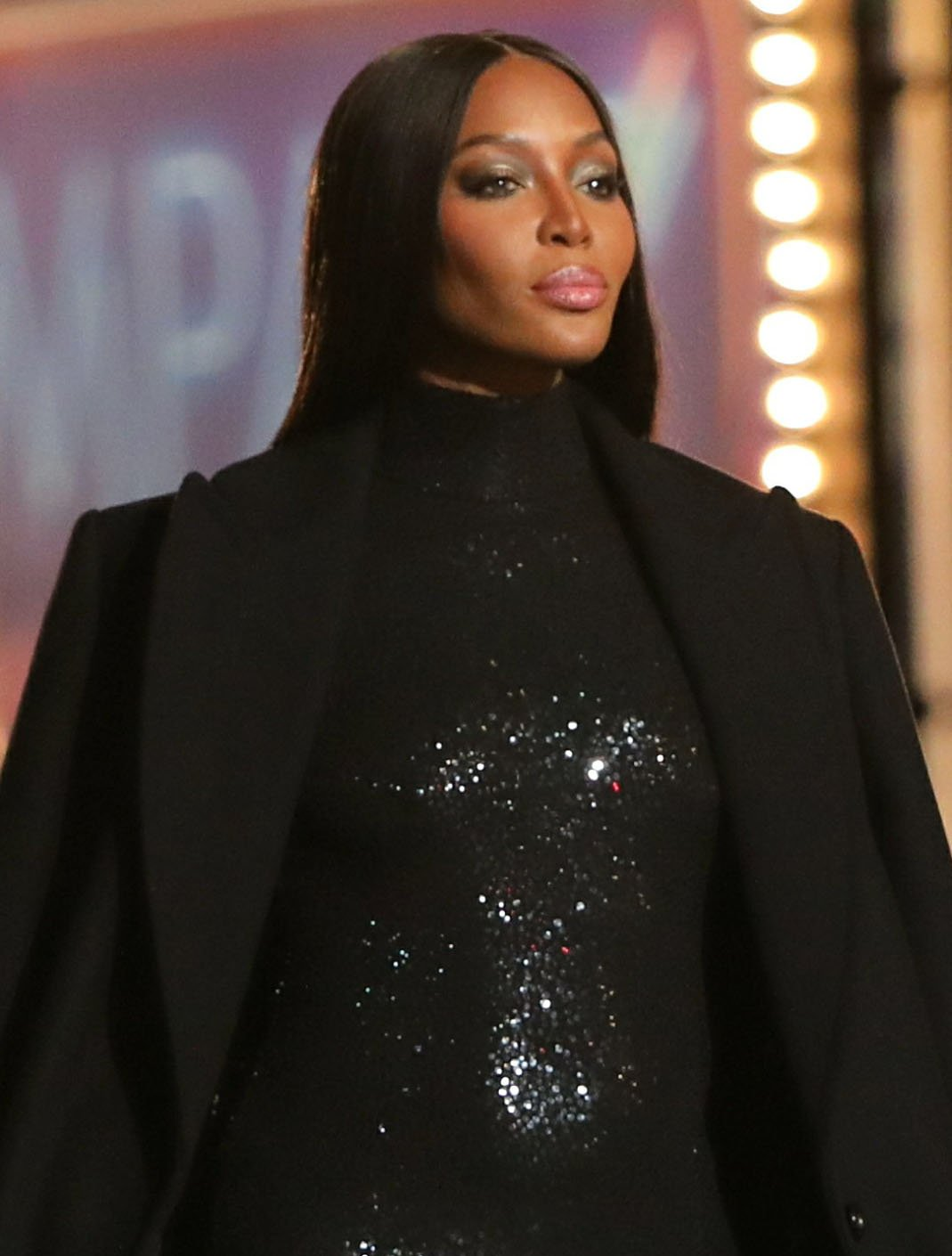Naomi Campbell wears her hair sleek straight with a middle parting