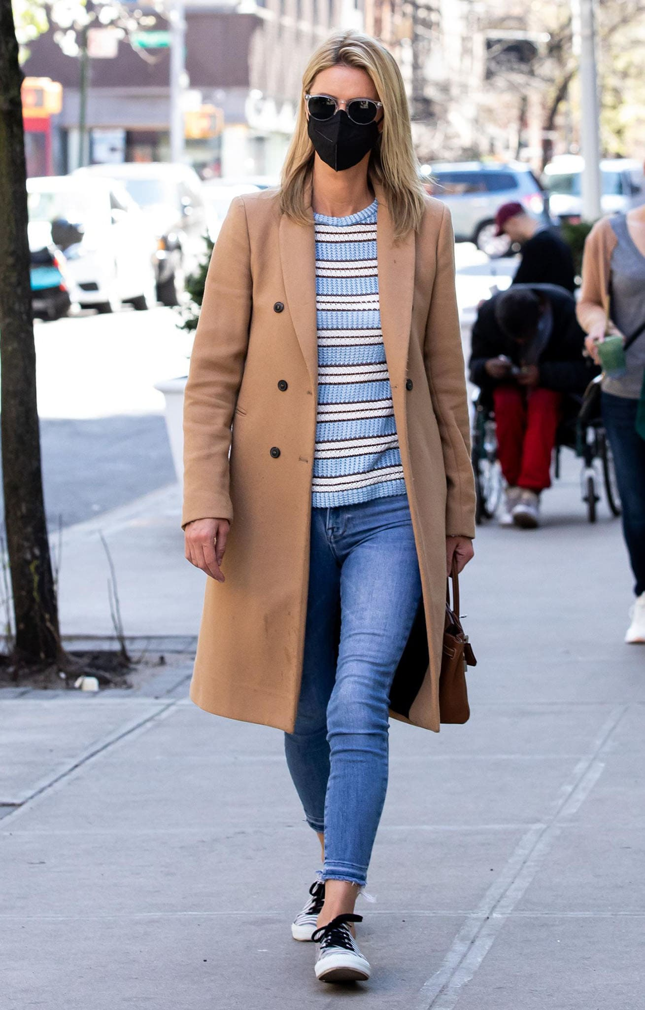 Nicky Hilton steps out in a striped sweater with jeans and a tan coat in SoHo on April 7, 2021