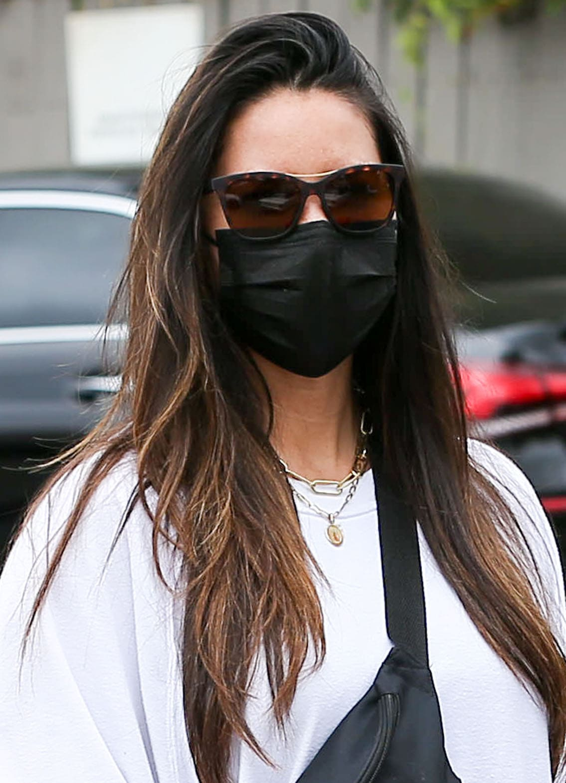 Olivia Munn wears a side-swept hairstyle and covers her eyes with Smith tortoiseshell sunglasses
