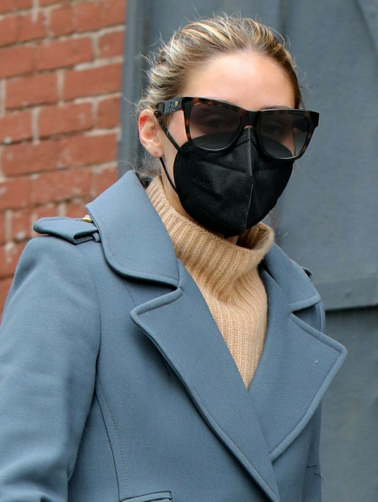 Olivia Palermo ties her hair in a bun and covers her face with tortoiseshell sunglasses and a black face mask