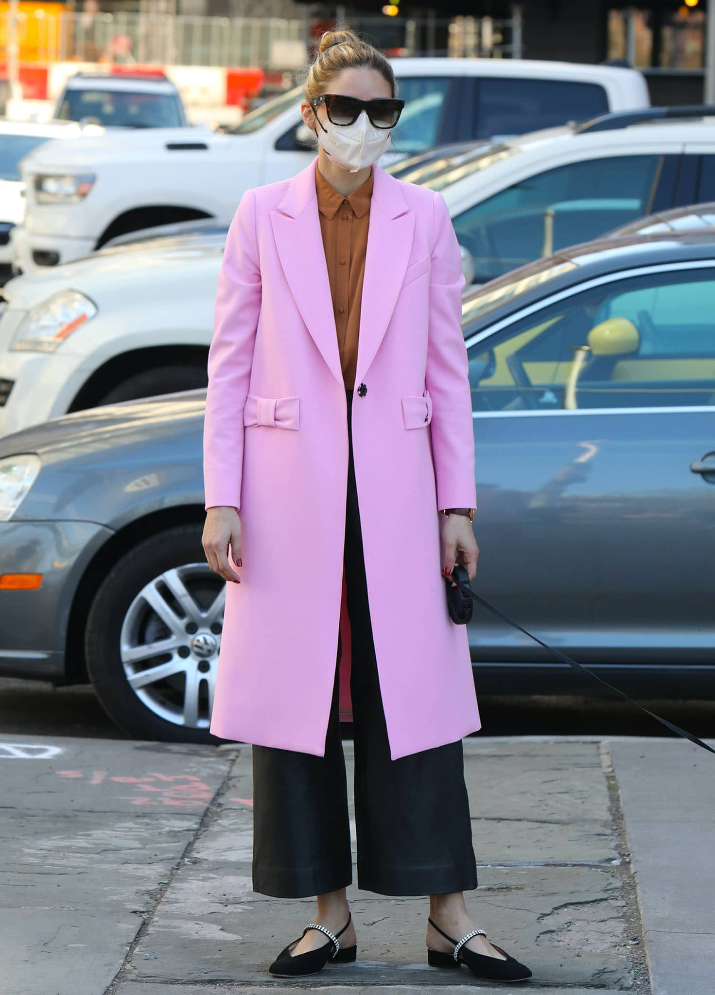 Olivia Palermo steps out in a feminine petal-pink Smythe bow coat and black wide-leg pants on March 30, 2021