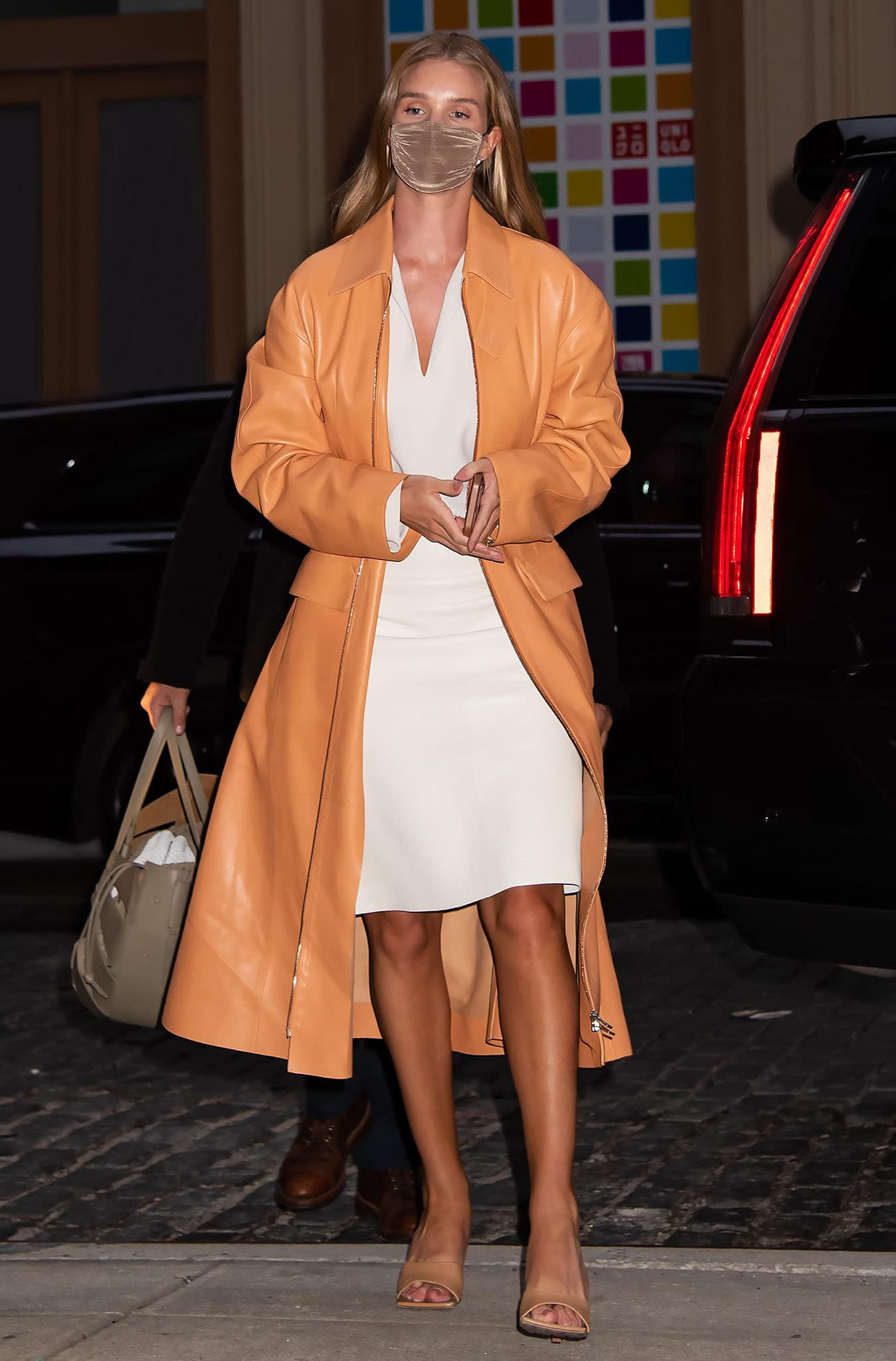 Rosie Huntington-Whiteley shows spring-chic in Bottega Veneta coral orange trench coat, Toteme cream blouse, and Bottega Veneta leather skirt
