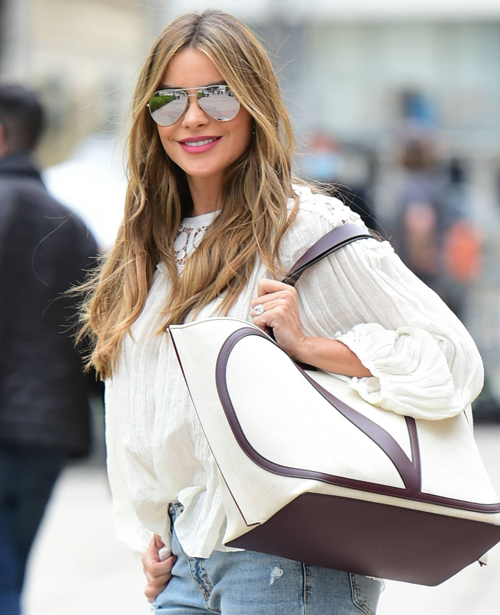 Sofia Vergara wears a wavy hairstyle and carries a Valentino Escape V-logo tote