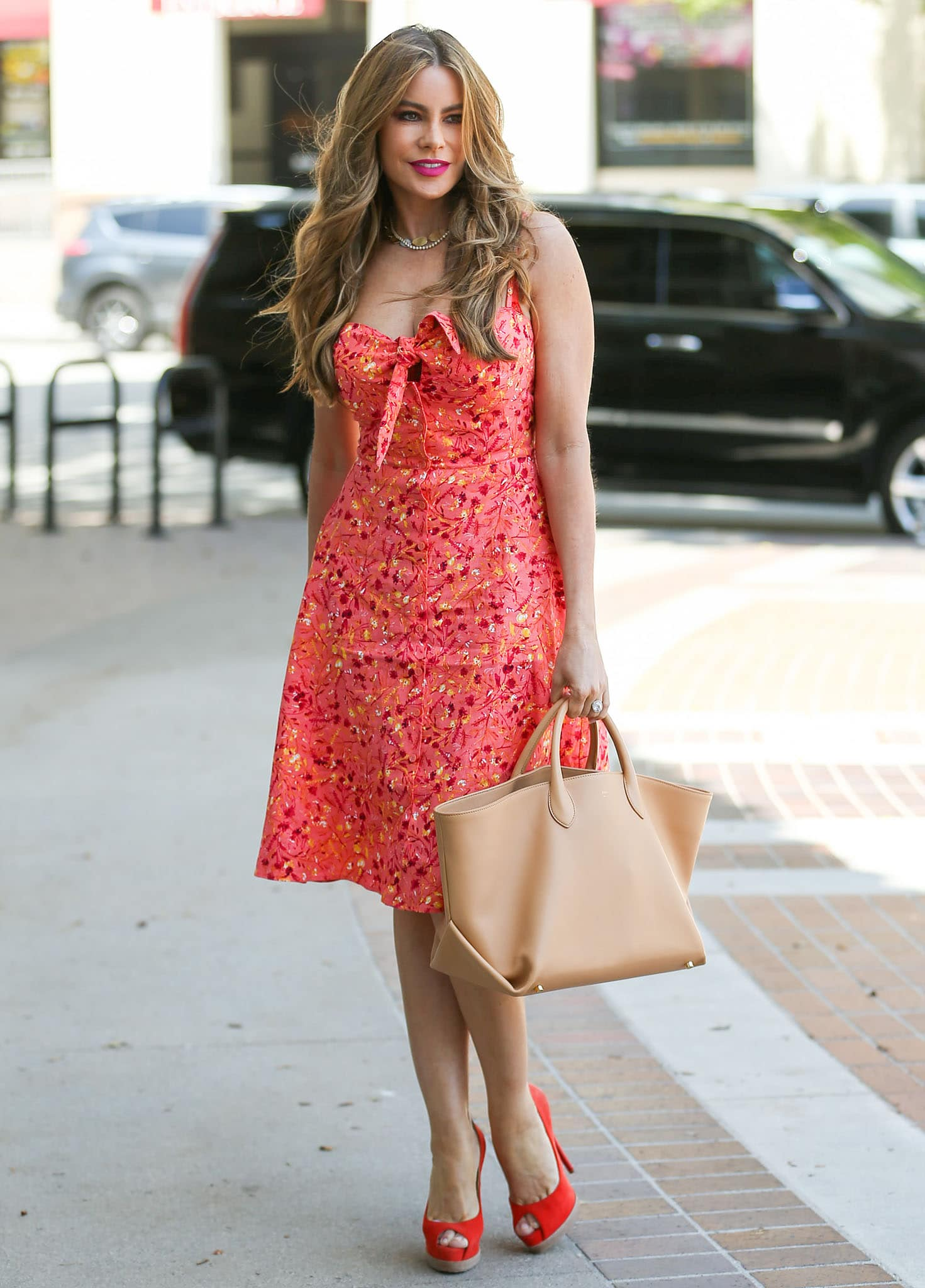 Sofia Vergara slips her curves into a flirty coral mini dress from her Sofia Jeans collection on April 16, 2021