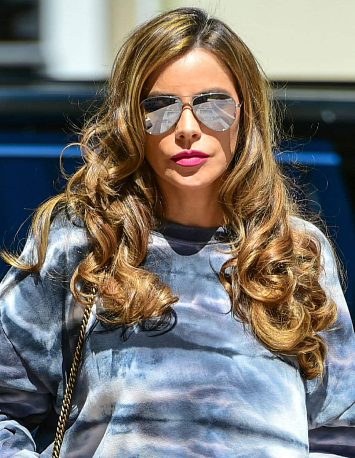 Sofia Vergara wears her signature curls and pink lipstick