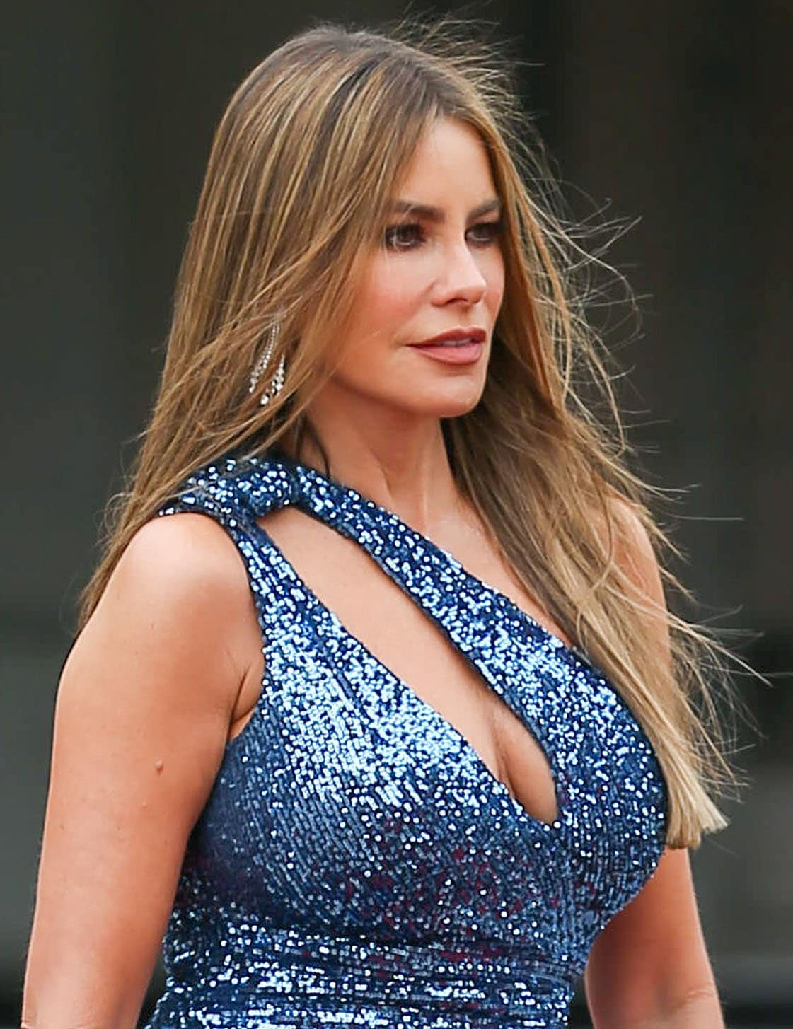 Sofia Vergara styles her look with diamond chandelier earrings and wears a full face of makeup