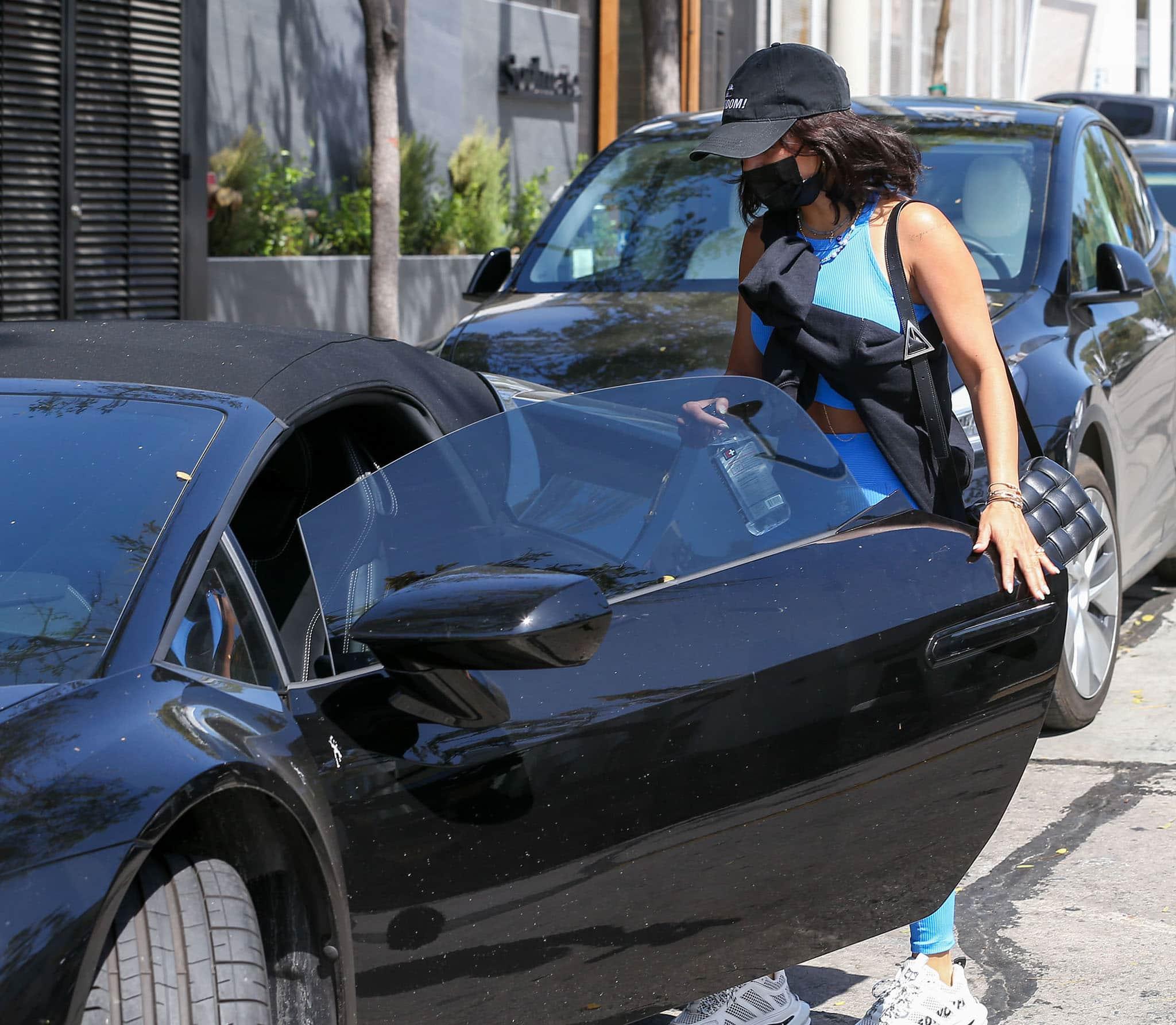 Vanessa Hudgens carries a Bottega Veneta bag as she gets in her black convertible car