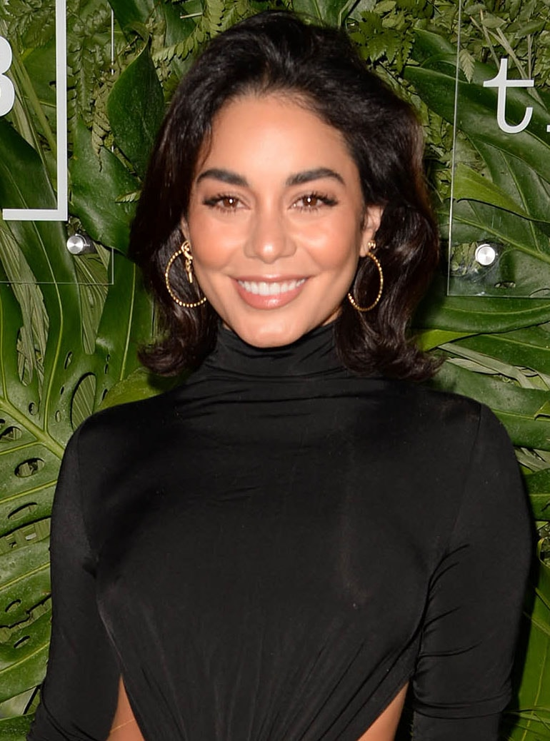 Vanessa Hudgens wears peachy makeup and a slightly teased wavy hairstyle