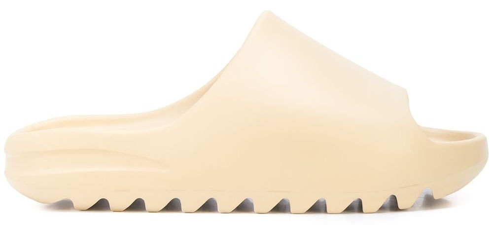 The Yeezy slide has a distinct silhouette with a shark-tooth rubber sole and a chunky upper