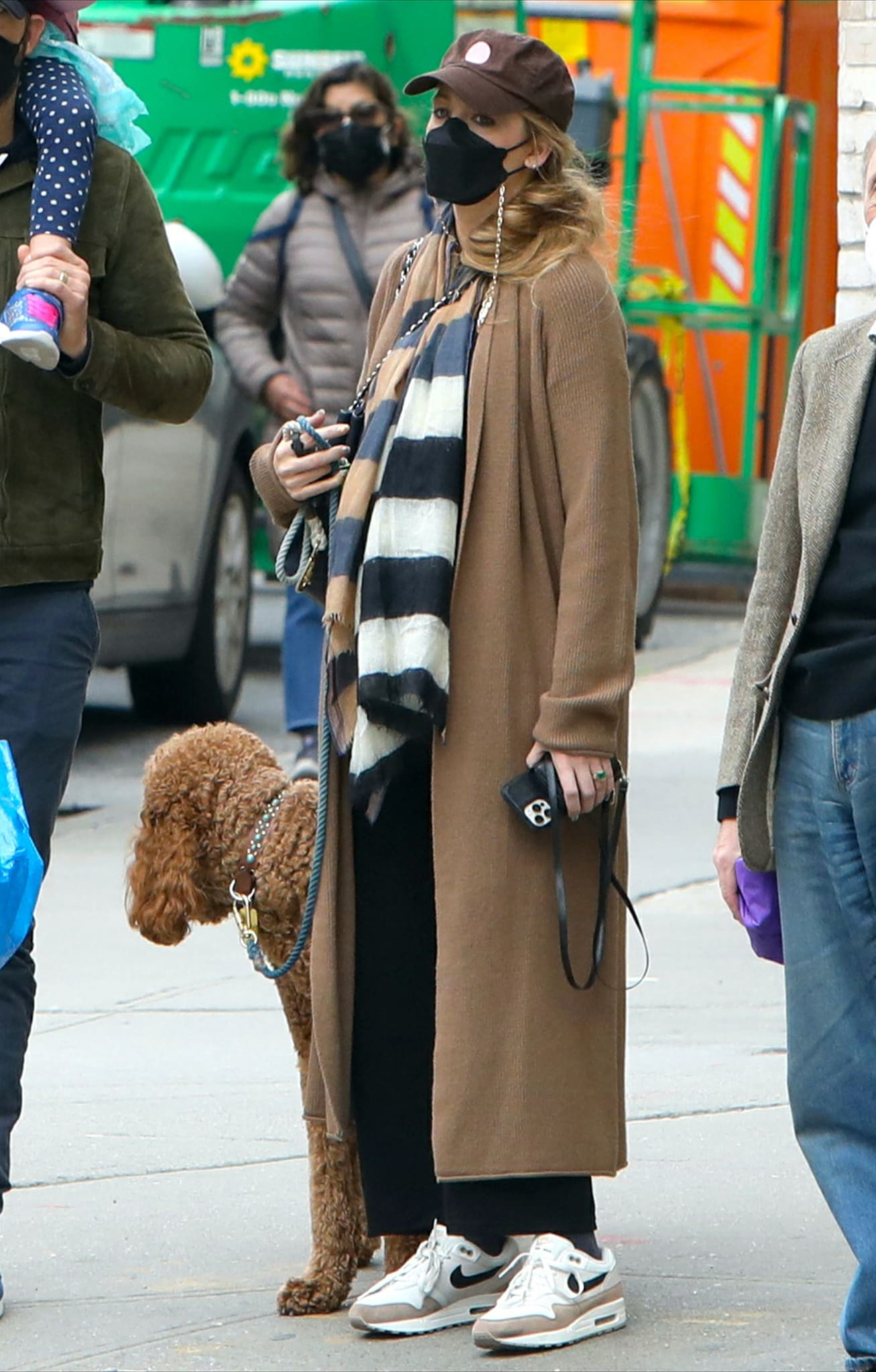Blake Lively bundles up in an ankle-length cardigan with a striped scarf and loose-fitting black pants