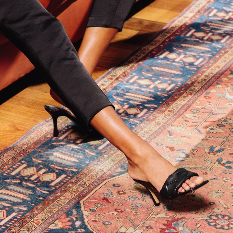Styled with an open square toe and woven footbed, this black mule is set on a flared high heel