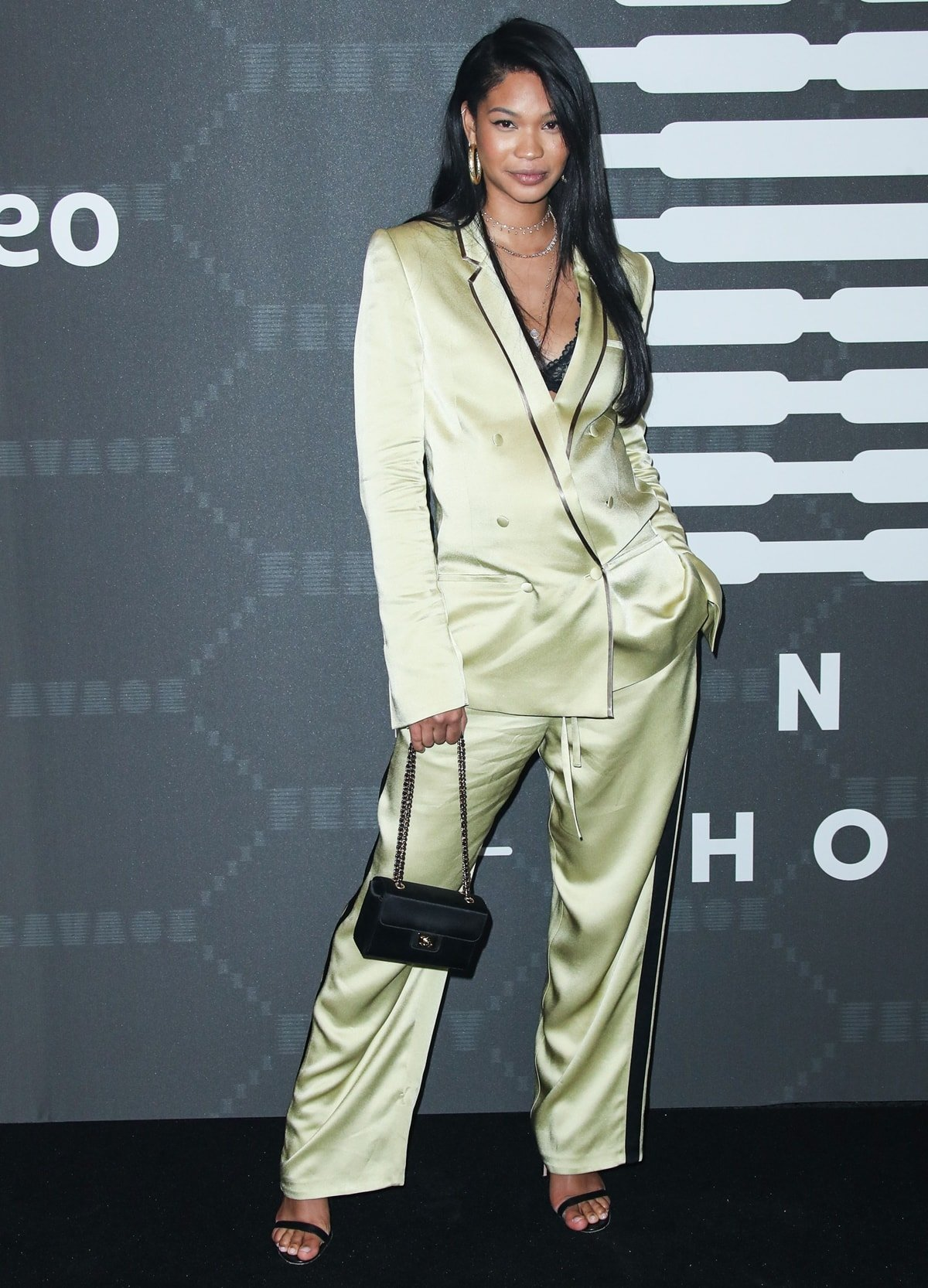 Chanel Iman wears a yellow-green pajama set and totes a Chanel bag at the Savage X Fenty Show